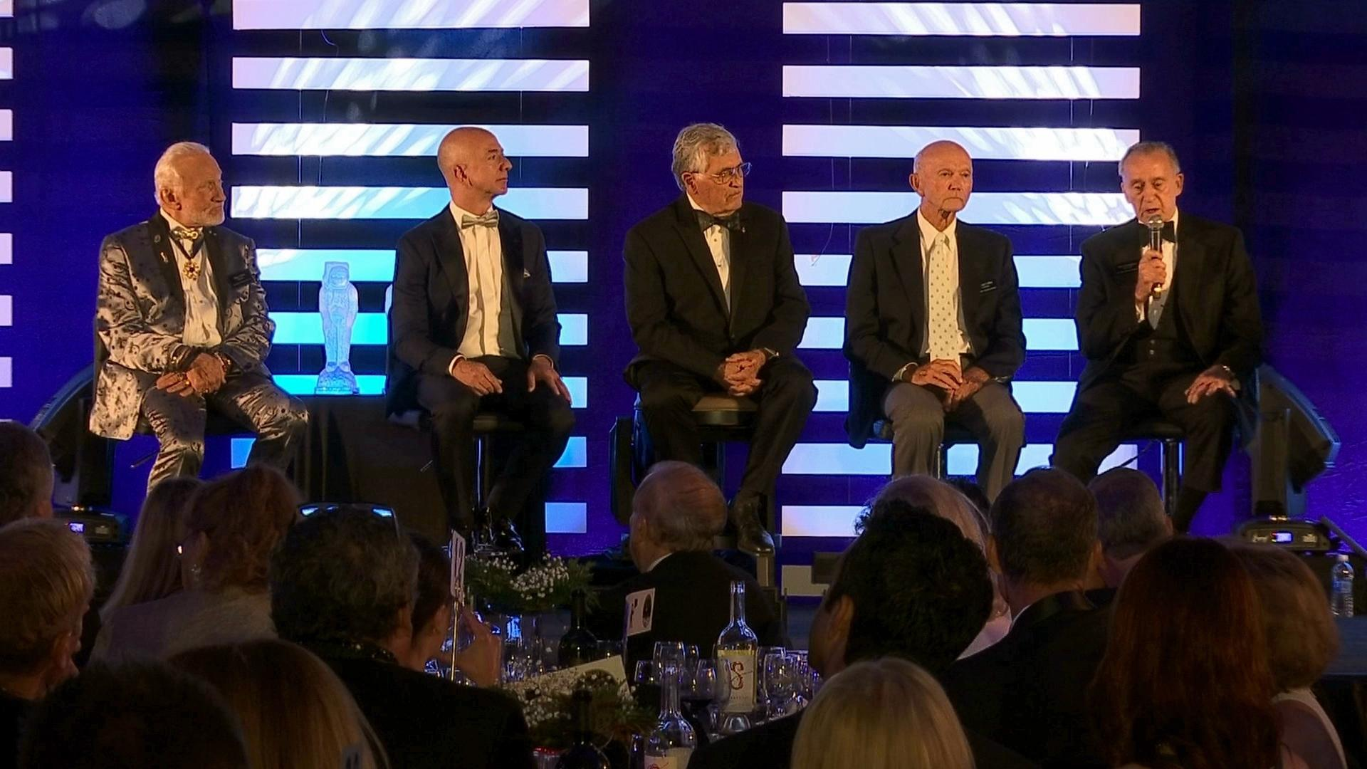 From left to right, Apollo 11 astronaut Buzz Aldrin, Amazon.com and Blue Origins founder Jeff Bezos, Apollo 17 astronaut Harrison Jack Schmitt, and Apollo 11 astronaut Michael Collins listen as Apollo 7 astronaut Walt Cunningham speaks during the commemoration for the upcoming anniversary of the 1969 mission to the moon and a gala for Aldrin's non-profit space education foundation, ShareSpace Foundation, at the Kennedy Space Center in Cape Canaveral, Fla., on Saturday, July 15, 2017. (AP Photo/Alex Sanz)