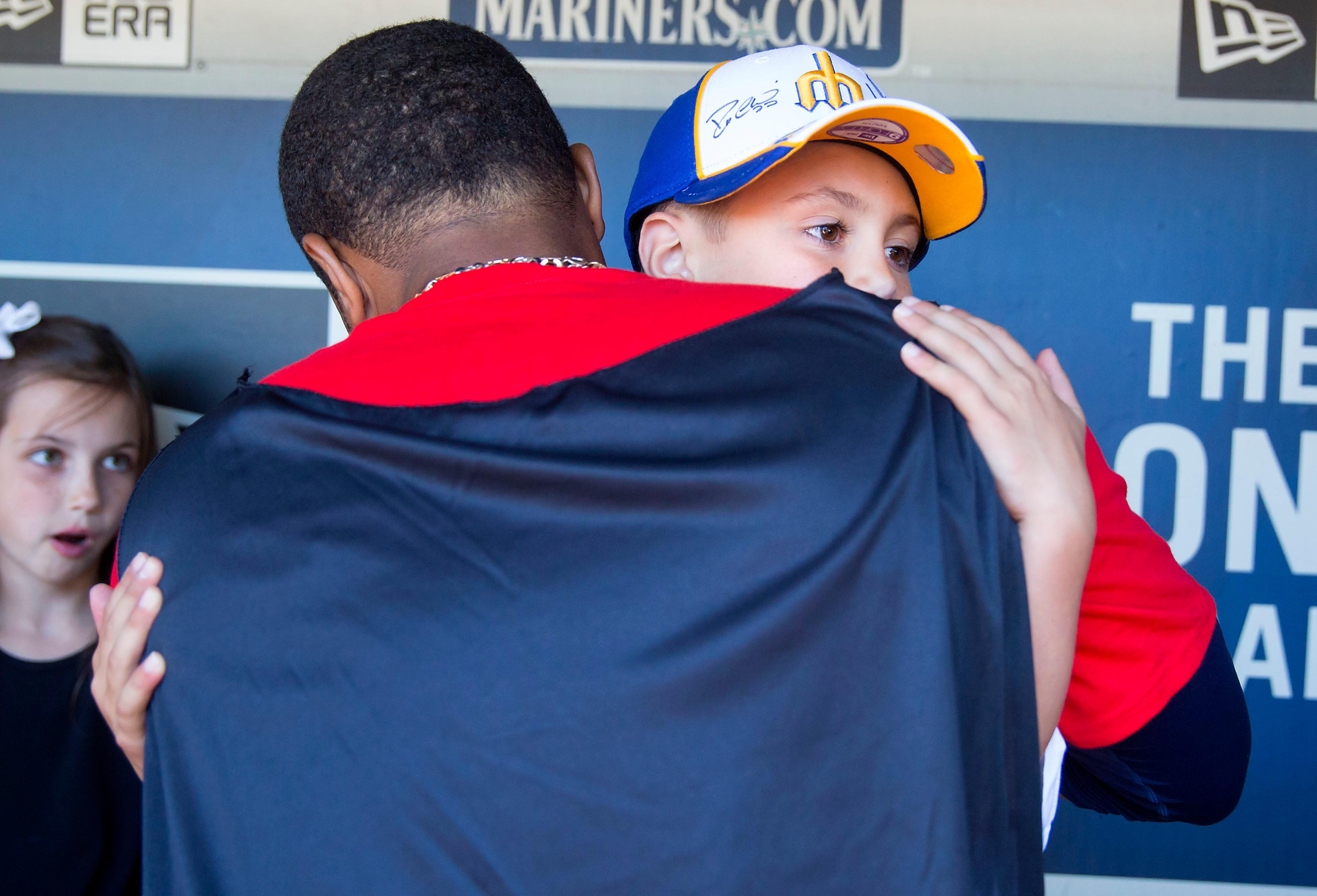 "Seven-year-old kidney cancer survivor Mason Nettleton hugs Seattle Mariners Robinson Cano's superhero costume as Nettleton served Seattle as a ""Superhero for a Day"" on Tuesday, June 27, 2017. (Sy Bean/ Seattle Refined)"