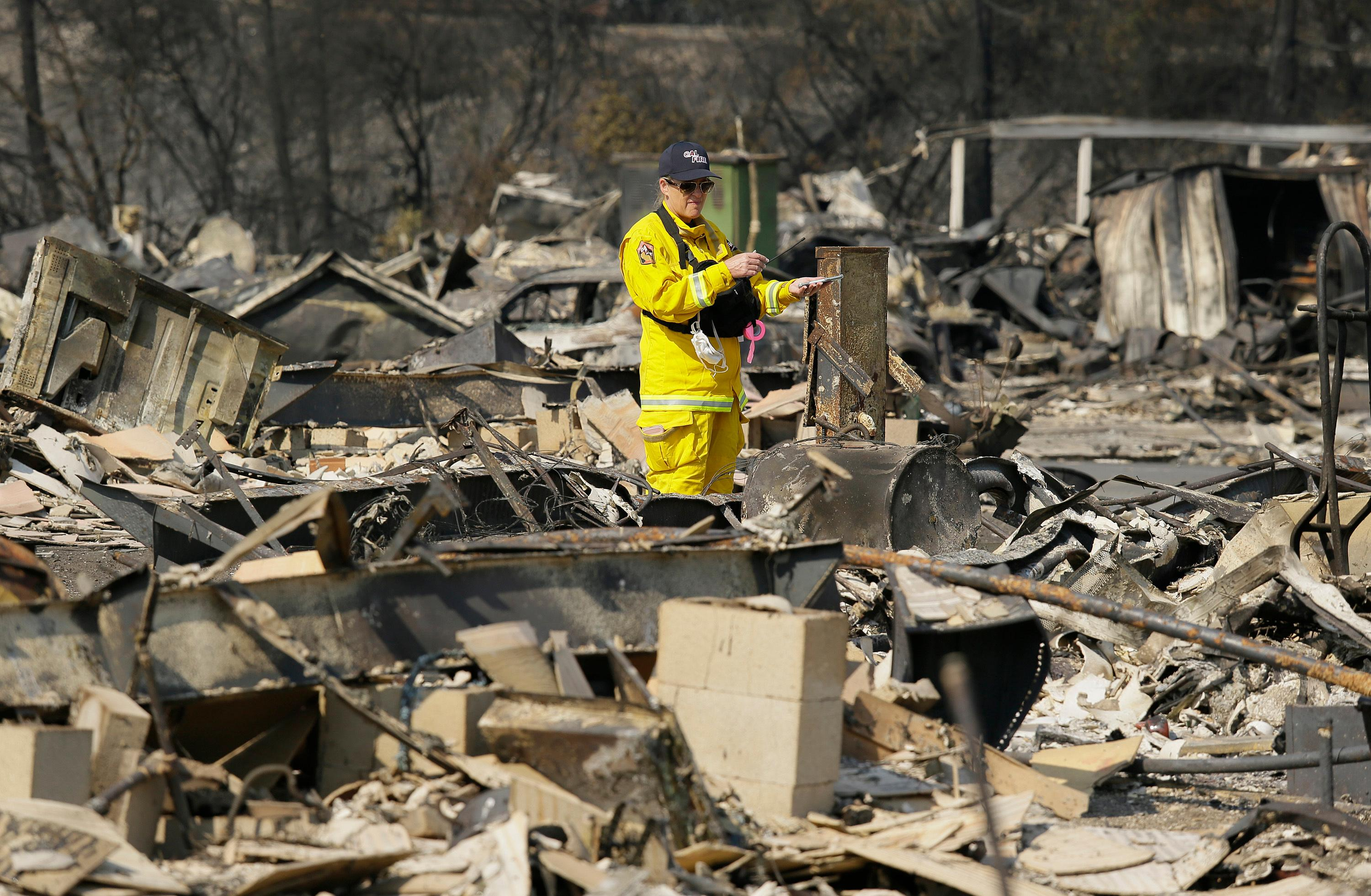 A Cal Fire official looks out at the remains of the Journey's End mobile home park Wednesday, Oct. 11, 2017, in Santa Rosa, Calif.    Blazes burning in Northern California have become some of the deadliest in state history. (AP Photo/Eric Risberg)