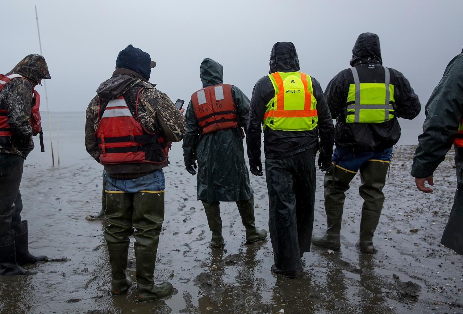Workers wait to board a boat that will take them out into Samish bay to tour the oysters and clams from Taylor Shellfish Farms. The company has its roots in shellfish farming in Washington State since the 1890s, and is now a proud leader of sustainable farming practices. (Sy Bean / Seattle Refined)