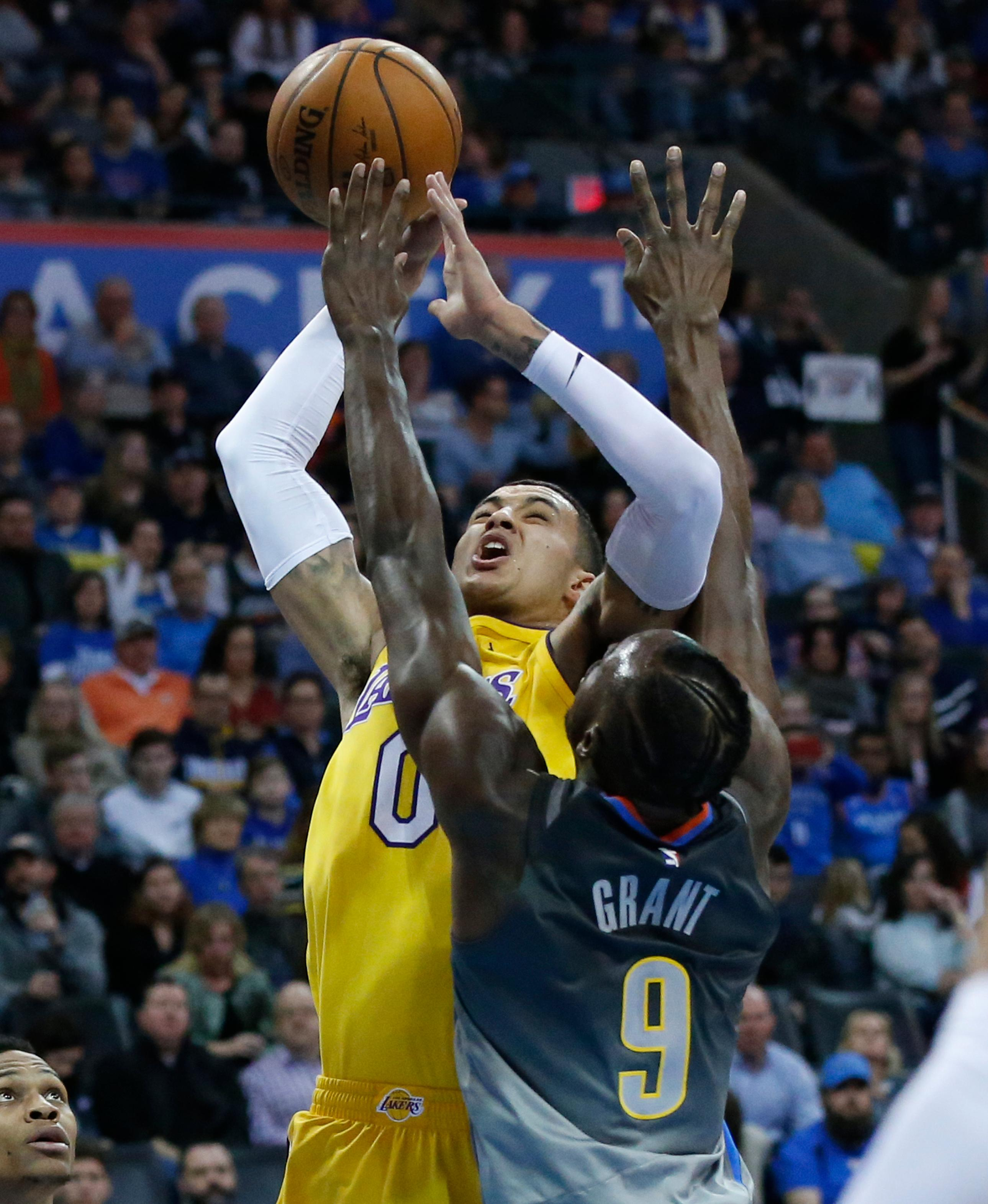 Los Angeles Lakers forward Kyle Kuzma (0) shoots as Oklahoma City Thunder forward Jerami Grant (9) defends in the first half of an NBA basketball game in Oklahoma City, Sunday, Feb. 4, 2018. (AP Photo/Sue Ogrocki)