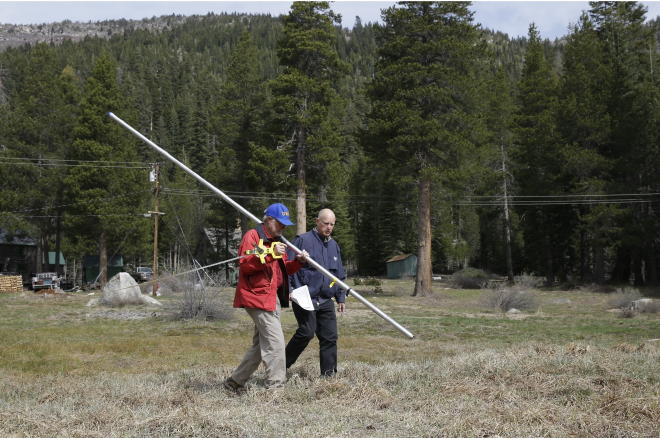 FILE - In this April 1, 2015 file photo, Frank Gehrke, chief of the California Cooperative Snow Surveys Program for the Department of Water Resources, and Gov. Jerry Brown walk across a dry meadow that is usually covered in several inches of snow to conduct a snow survey, near Echo Summit, Calif.  More than 40 percent of California has emerged from a punishing drought that covered the whole state a year ago, federal drought-watchers said Thursday, Jan. 12, 2017  a stunning transformation caused by an unrelenting series of storms in the North that filled lakes, overflowed rivers and buried mountains in snow. (AP Photo/Rich Pedroncelli, File)