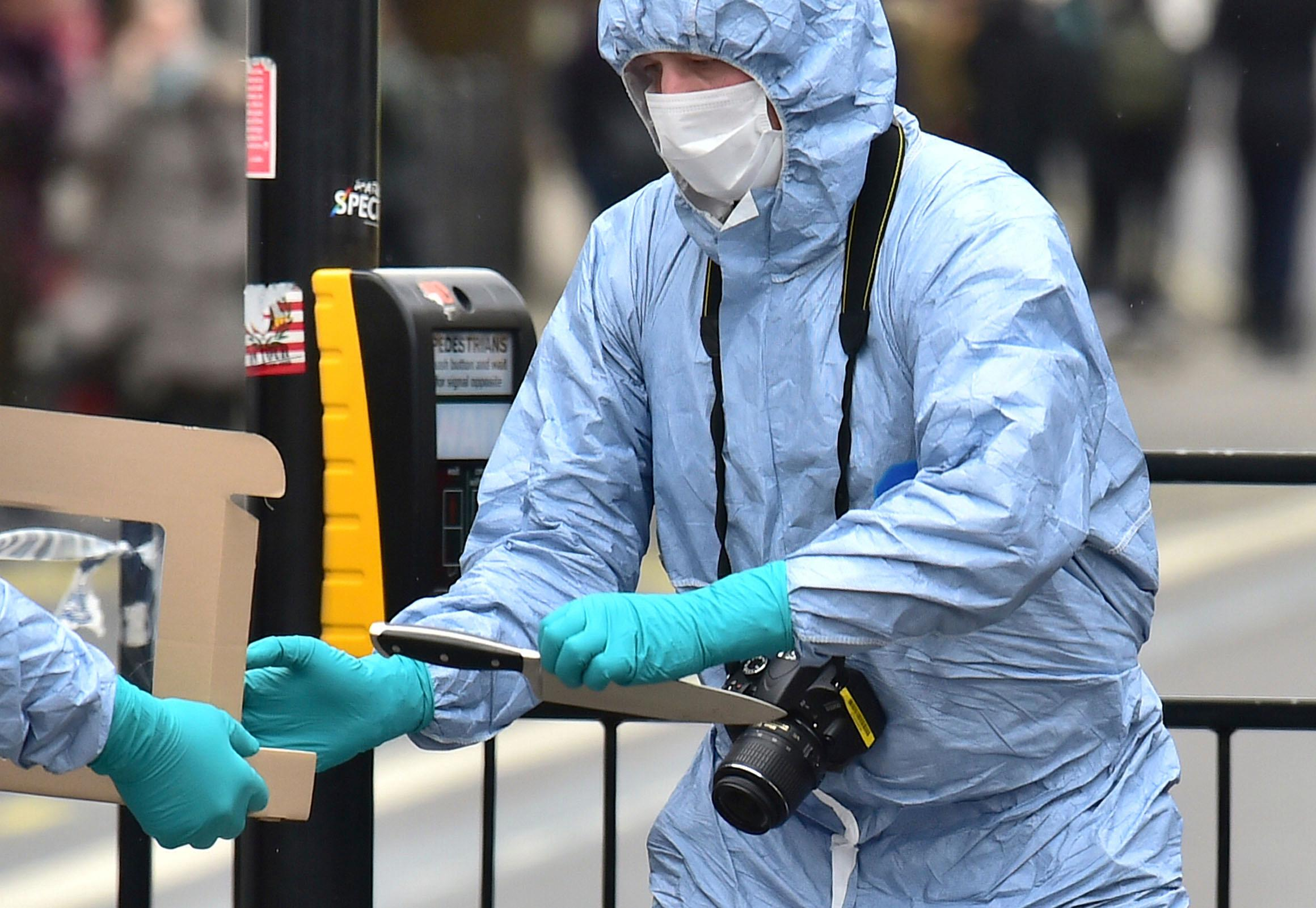 A police forensic officer holds a knife at the scene after a man was arrested following an incident at Whitehall in London, Thursday April 27, 2017.  London police arrested a man for possession of weapons Thursday near Britain's Houses of Parliament. (Dominic Lipinski/PA via AP)