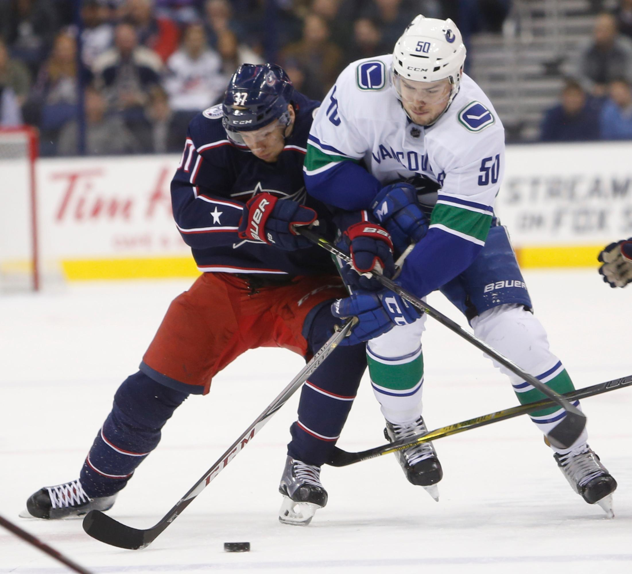 Columbus Blue Jackets' Markus Hannikainen, left, of Finland, and Vancouver Canucks' Brendan Gaunce fight for the puck during the first period of an NHL hockey game Friday, Jan. 12, 2018, in Columbus, Ohio. (AP Photo/Jay LaPrete)