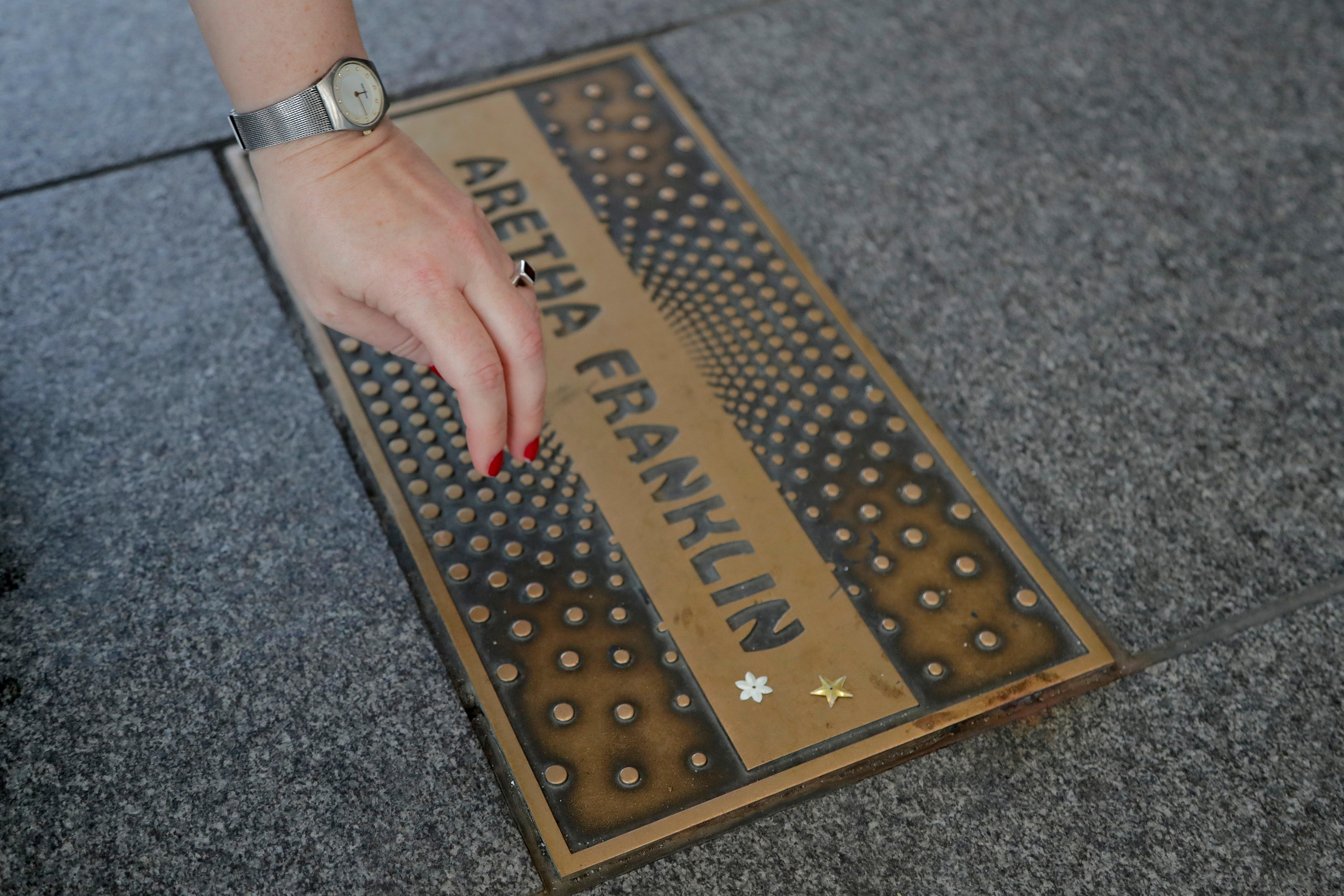 Agnieszka Mroczek, a tourist from Warsaw, Poland, pulls her hand away after placing stars on the nameplate for singer Aretha Franklin outside the Apollo Theater, Thursday, Aug. 16, 2018, in the Harlem section of New York. Franklin died in her home in Detroit at age 76 from pancreatic cancer. (AP Photo/Julio Cortez)