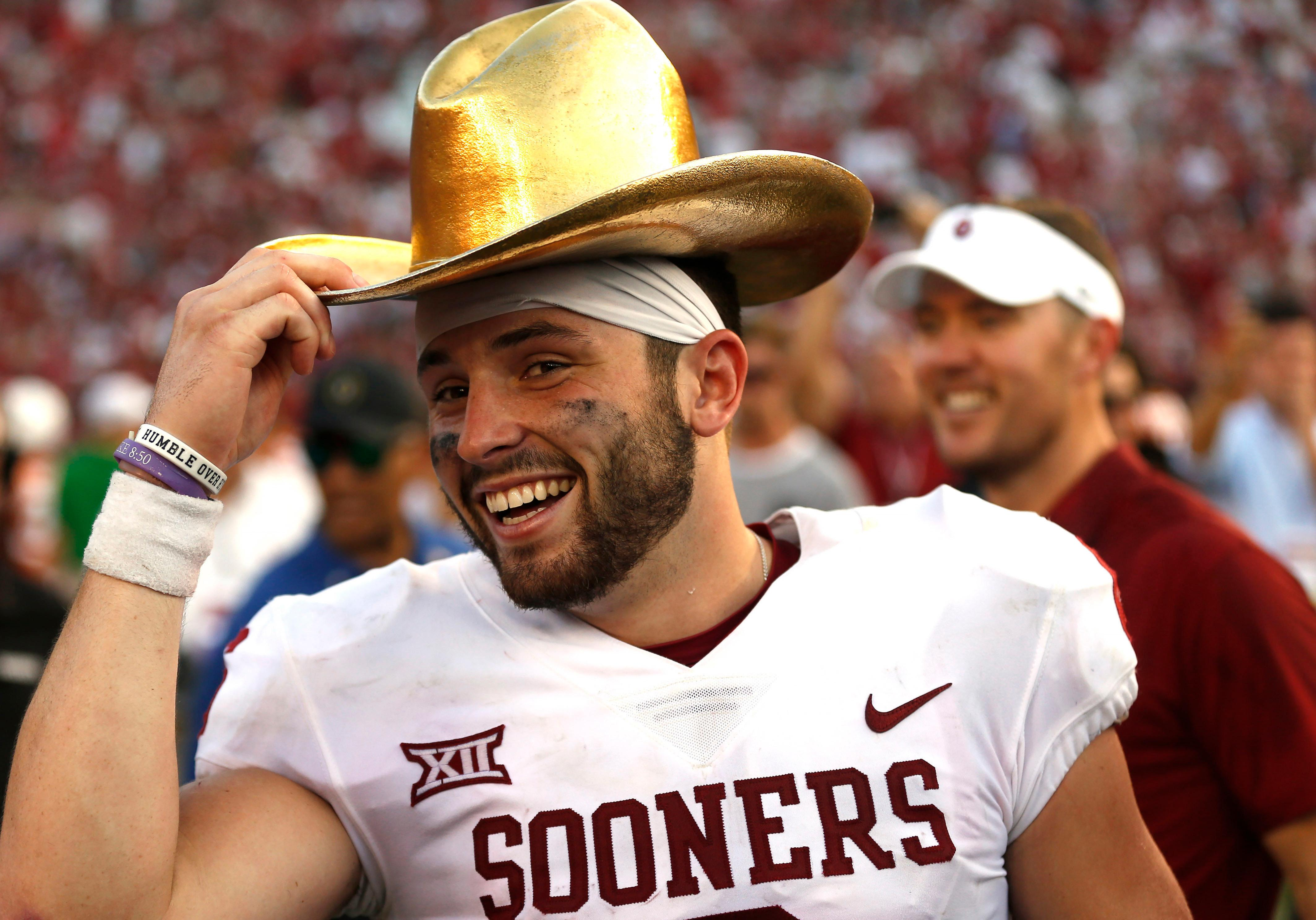 FILE - In this Oct. 14, 2017, file photo, Oklahoma quarterback Baker Mayfield (6) celebrates with the Golden Hat Trophy following the team's 29-24 win over Texas in an NCAA college football game in Dallas. Baker Mayfield is the AP player of the year, becoming the fourth Oklahoma quarterback to win the award since it was established in 1998.  (AP Photo/Ron Jenkins, File)