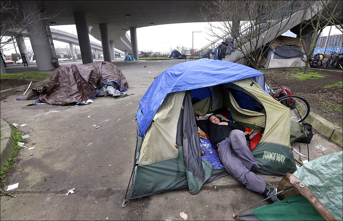 seattle in uncharted territory as homelessness spikes komo a man lies in a tent others camped nearby under and near an overpass