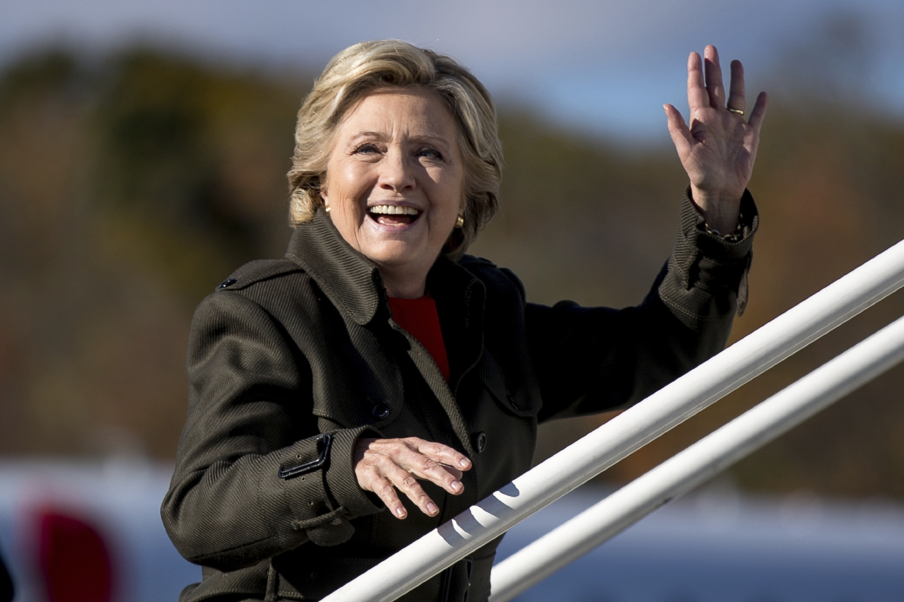 Democratic presidential candidate Hillary Clinton waves to members of the media as she boards her campaign plane at Westchester County Airport in White Plains, N.Y., Monday, Oct. 31, 2016, to travel to Cleveland for a rally. (AP Photo/Andrew Harnik)