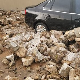 A reinforced rock wall collapsed, damaging businesses and cars in west El Paso. (Courtesy: Eli Camacho.