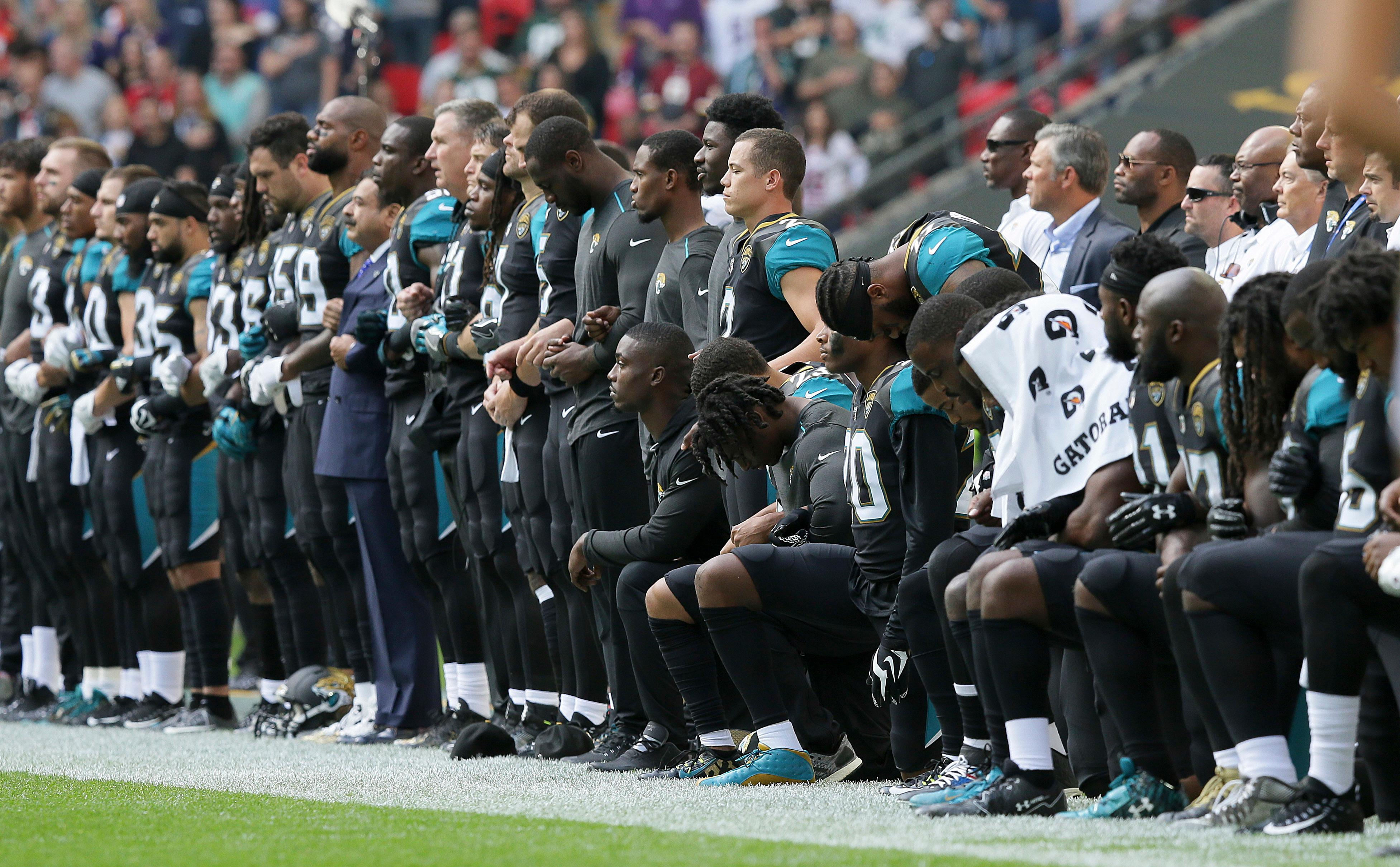 Jacksonville Jaguars players lock arms and kneel down during the playing of the U.S. national anthem before an NFL football game against the Baltimore Ravens at Wembley Stadium in London, Sunday Sept. 24, 2017. (AP Photo/Tim Ireland)