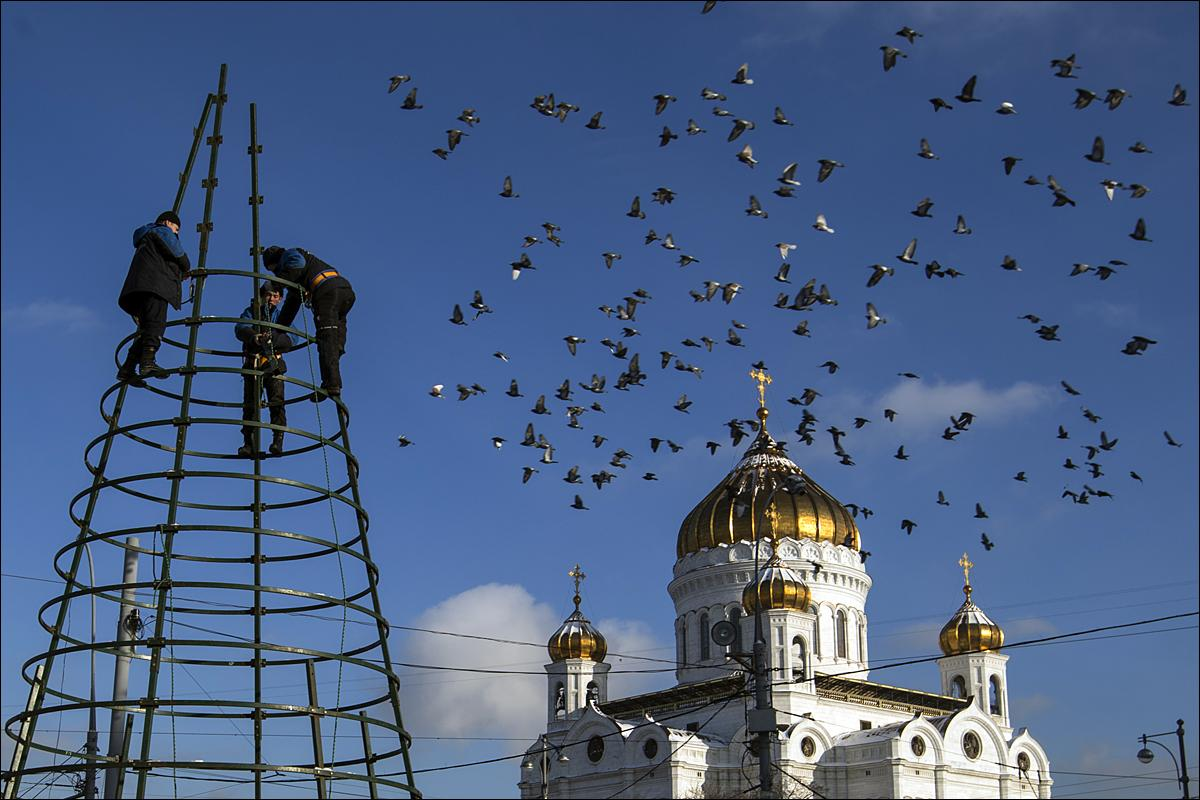 Municipal workers disassemble Christmas decorations in front of Christ the Savior Cathedral in Moscow, Thursday, Jan. 21, 2016. (AP Photo/Pavel Golovkin)