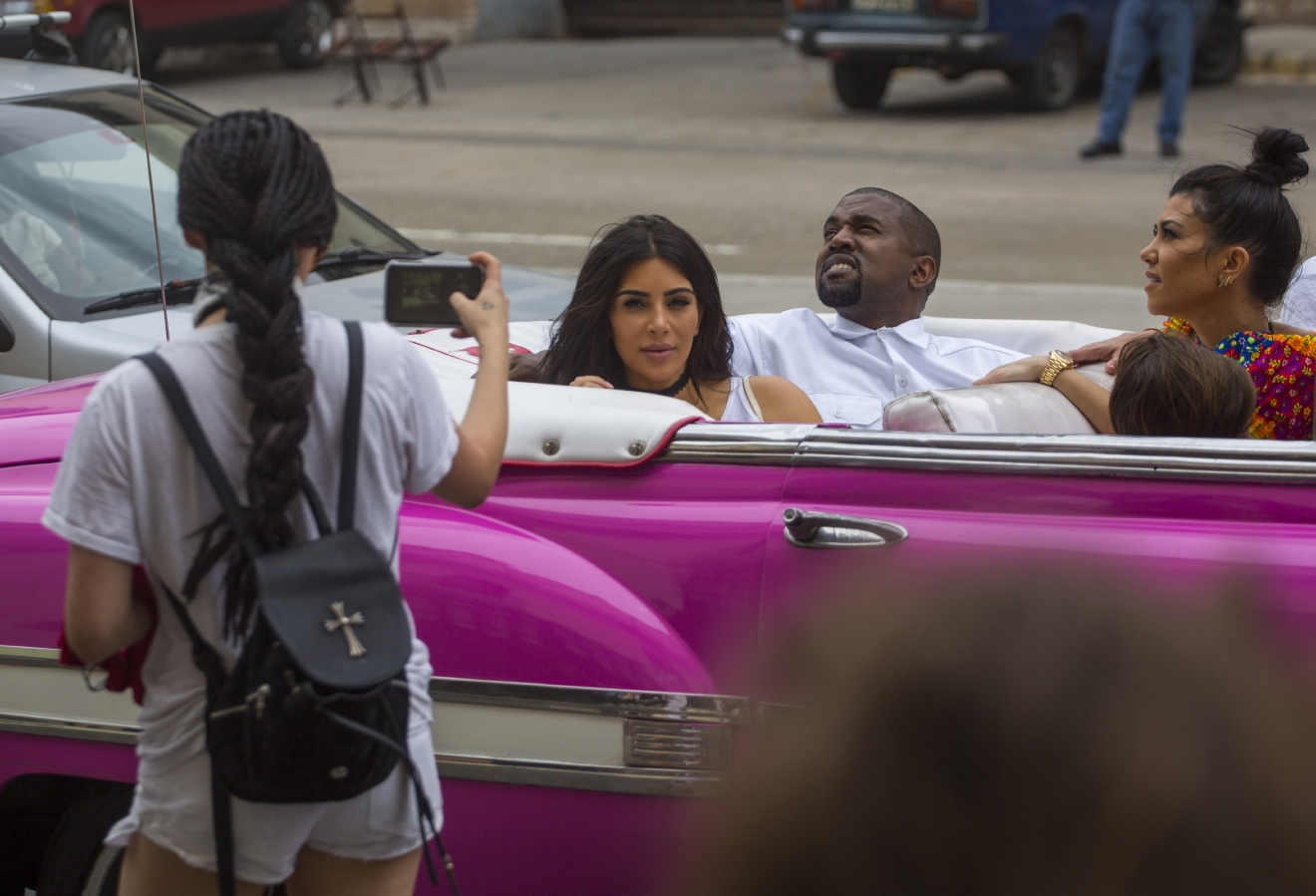 A woman uses her cellphone to take a picture American reality-show star Kim Kardashian West, center, and her husband Kayne West as they ride on a classic car along the streets of Havana, Cuba, Wednesday, May 4, 2016. Rap superstar Kayne West, his wife Kim Kardashian and members of her reality-show-star family have become the latest celebrities to visit Havana. They visited HavanaÂ?s Museum of Rum Wednesday, stepping out of a hot-pink antique American convertible as they snapped selfies and were recorded by a television crew following them around. At right is Kourtney Mary Kardashian,(AP Photo/Desmond Boylan)
