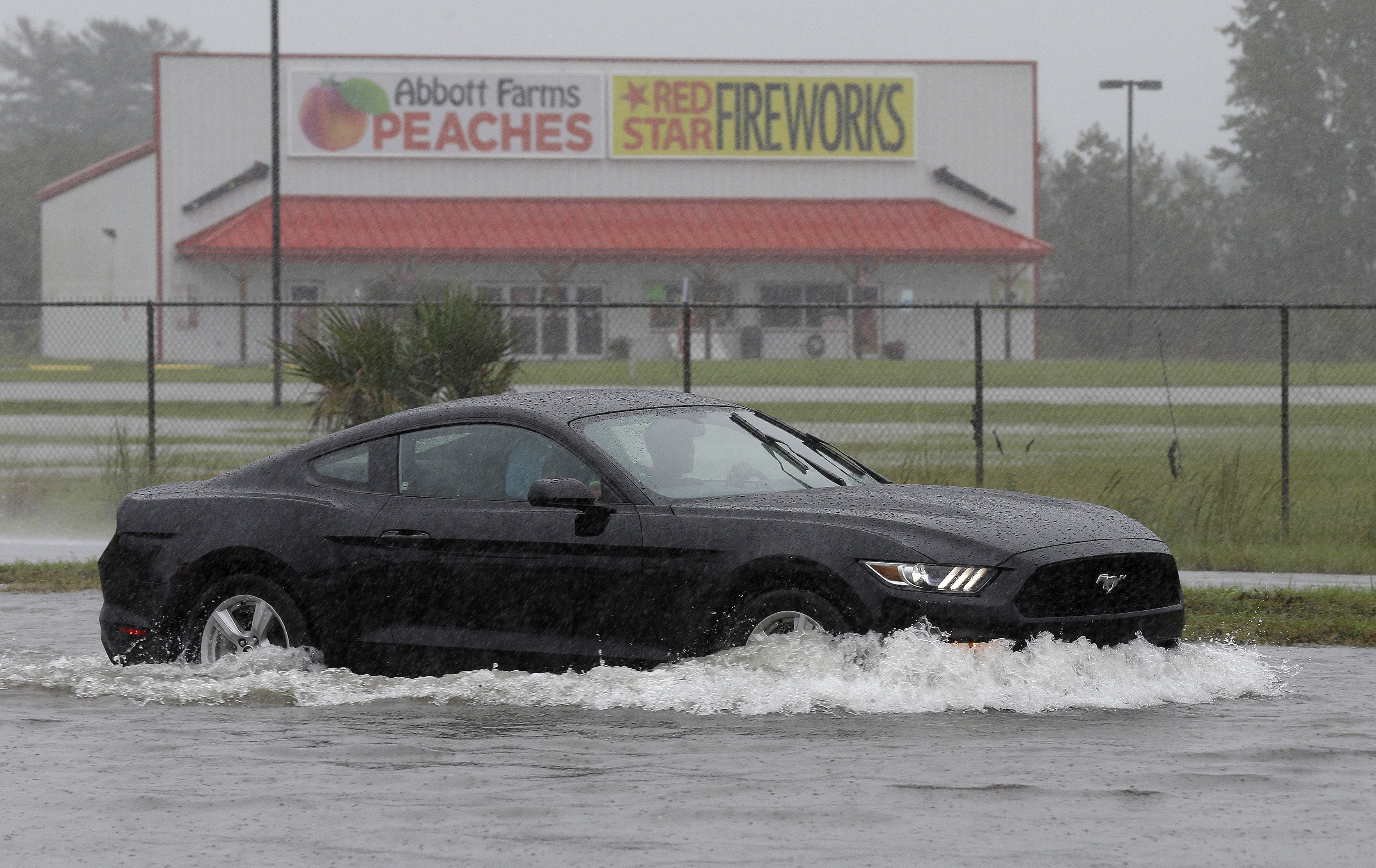 "A driver navigates a flooded road in Florence, S.C., Sunday, Oct. 4, 2015 as rain continues to cause flash flooding in some areas of the state. A dangerous rainstorm drenching the East Coast brought more misery Sunday to South Carolina, cutting power to thousands, forcing hundreds of water rescues and closing ""too many roads to name"" because of floodwaters. (AP Photo/Gerry Broome)"