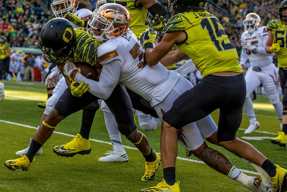 The Duck's Tony Brooks-James (#20) keeps a tight grip on the ball as a Sun Devils player grabs on for the ride. Oregon lead at the end of the 1st half 30-14. Photos by August Frank, Oregon News Lab