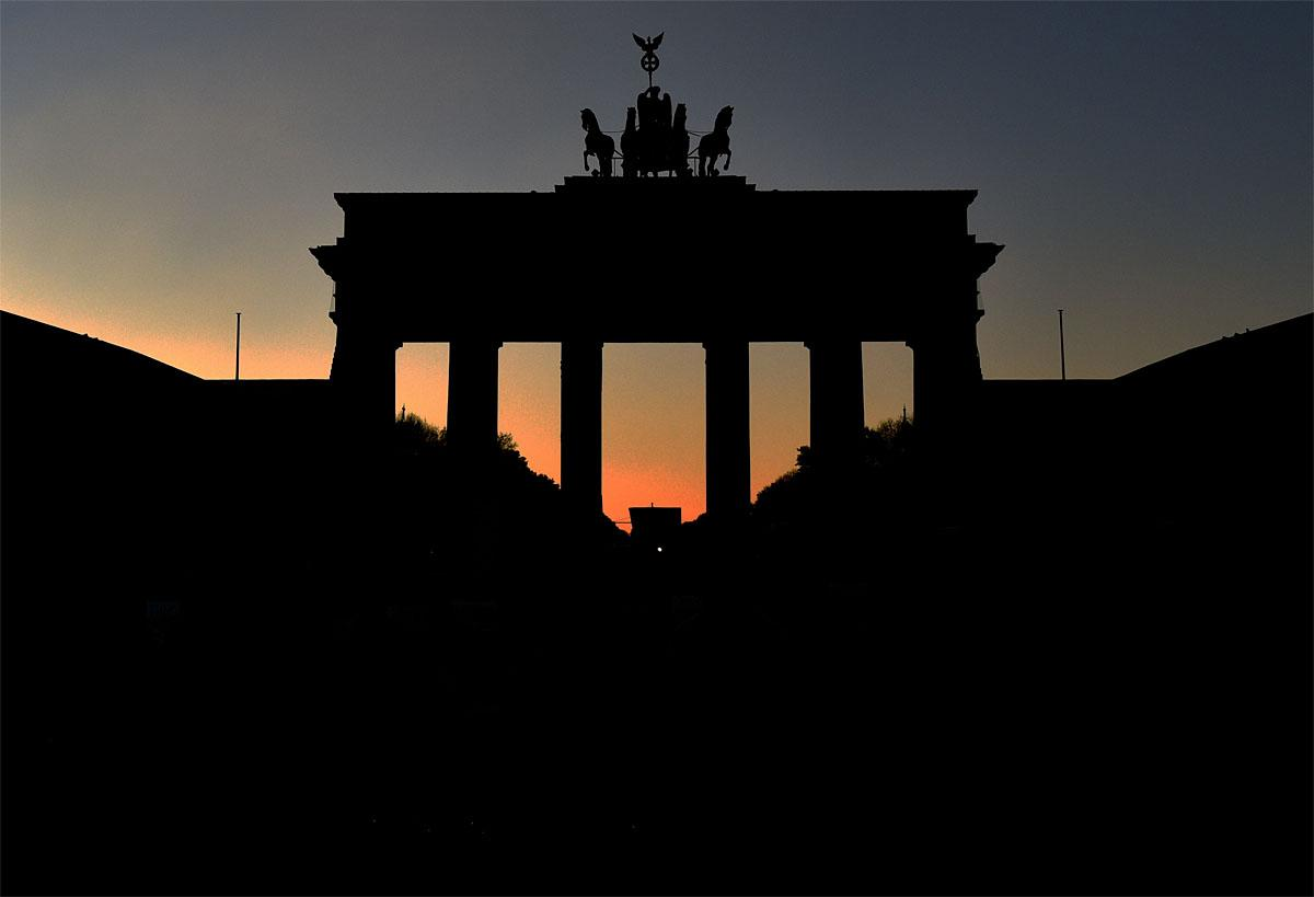 The sun sets behind the silhouetted Brandenburg Gate in Berlin, Germany, Saturday Nov. 12, 2016. ( Ralf Kirschberger/dpa via AP)
