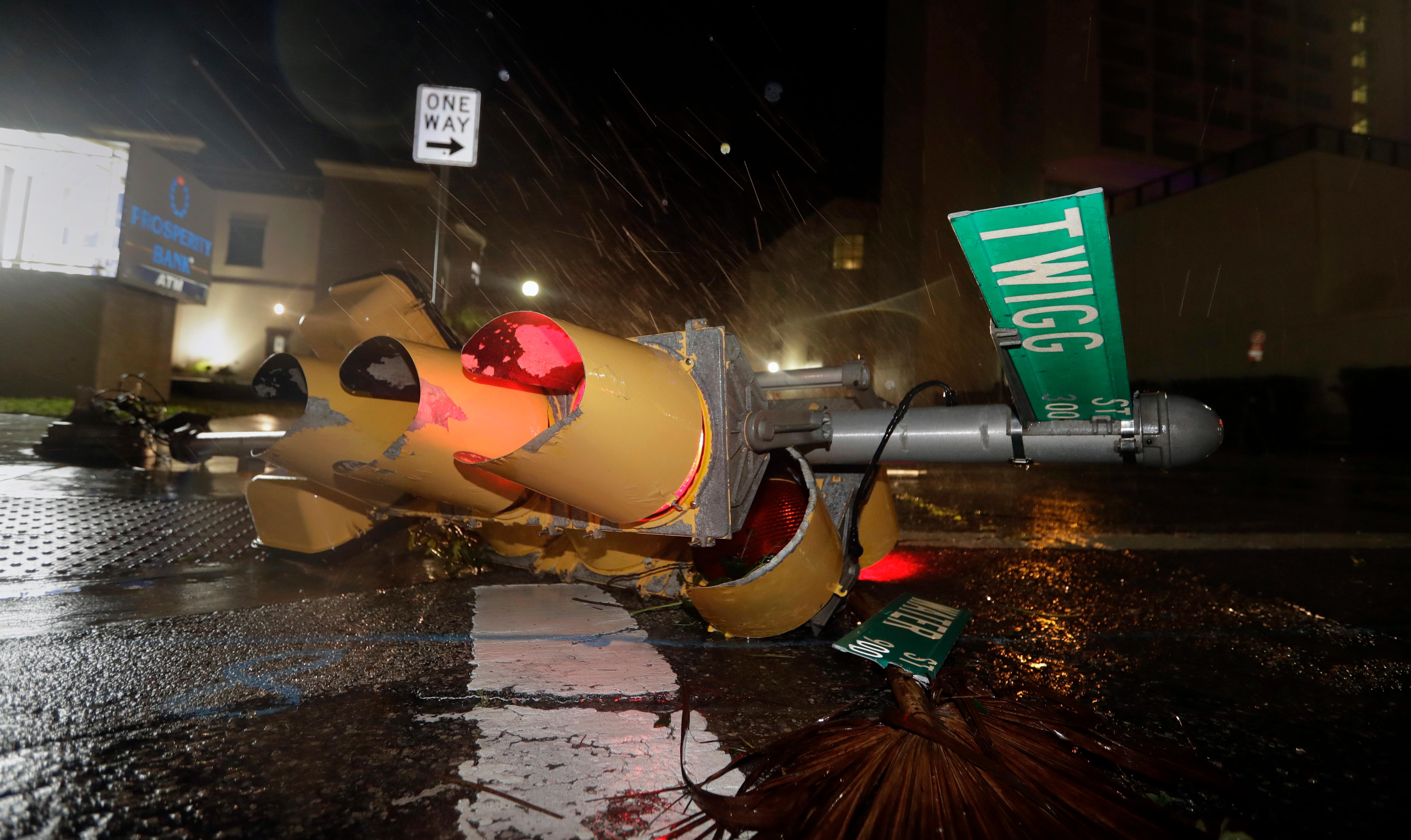 A traffic signal topped by the winds of Hurricane Harvey lies in an intersection of downtown Corpus Christi, Texas, Saturday, Aug. 26, 2017.  Harvey has been further downgraded to a Category 1 hurricane as it churns slowly inland from the Texas Gulf Coast, already depositing more than 9 inches of rain in South Texas. (AP Photo/Eric Gay)