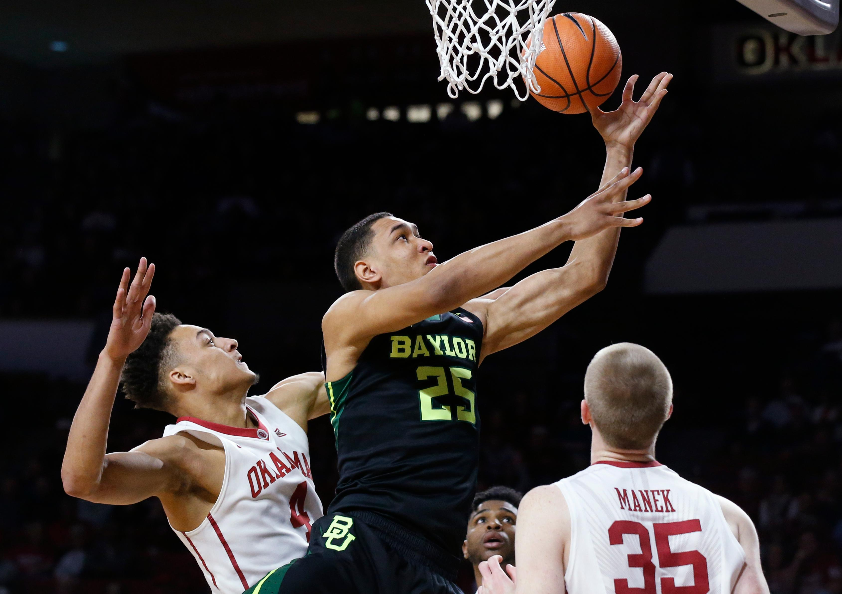 Baylor forward Tristan Clark (25) shoots between Oklahoma center Jamuni McNeace (4) and forward Brady Manek (35) during the first half of an NCAA college basketball game in Norman, Okla., Tuesday, Jan. 30, 2018. (AP Photo/Sue Ogrocki)