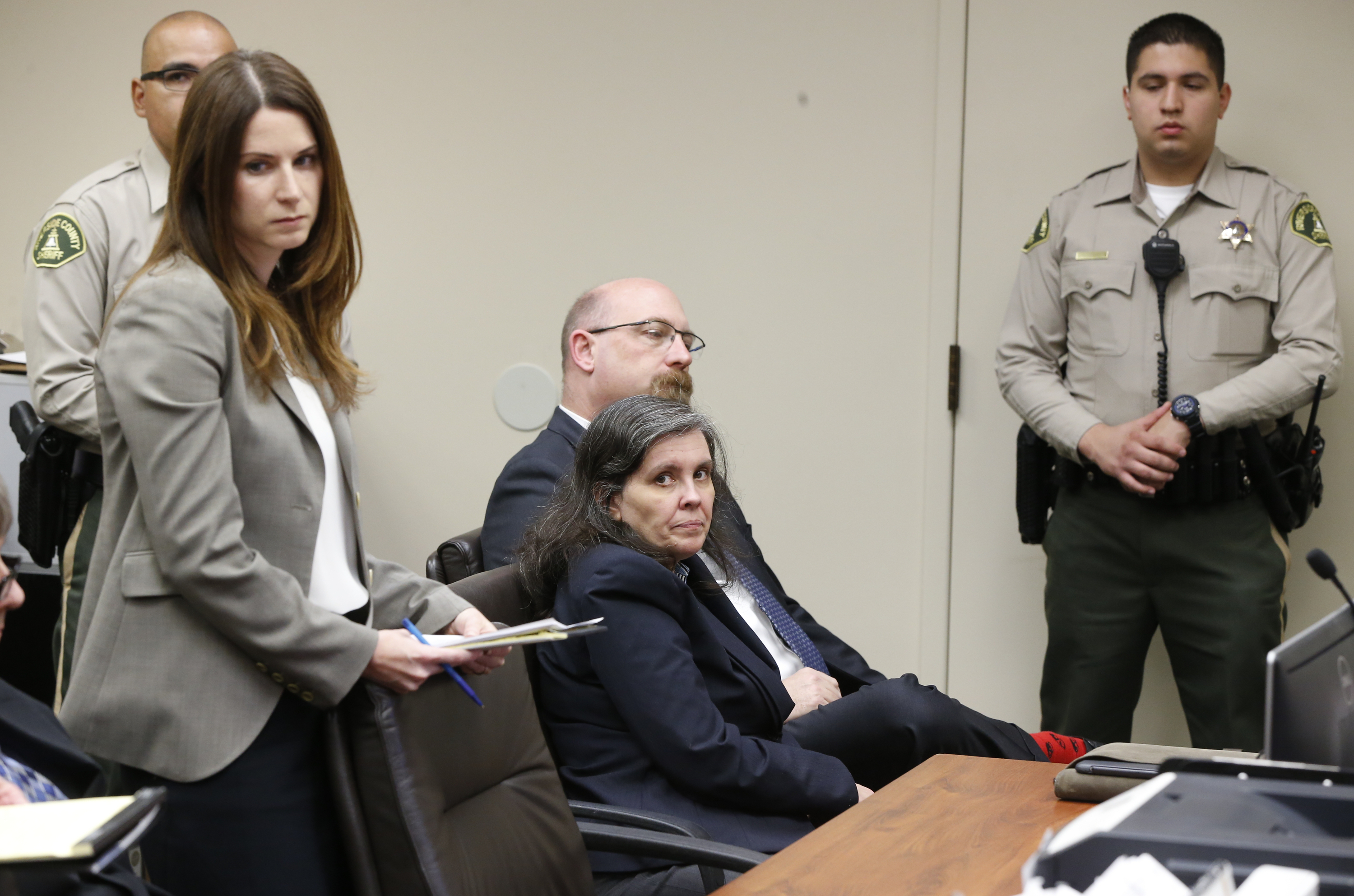Louise Turpin, center, sits with her counsel, Jeff Moore, as she appears in court for a conference about she and her husband's case in Riverside, Calif., Friday, Feb. 23, 2018. David and Louse Turpin have pleaded not guilty to torture and other charges and each is held on $12 million bail. The couple was arrested last month after their 17-year-old daughter escaped from the family's home in Perris, Calif., and called 911. (AP Photo/Damian Dovarganes, Pool)