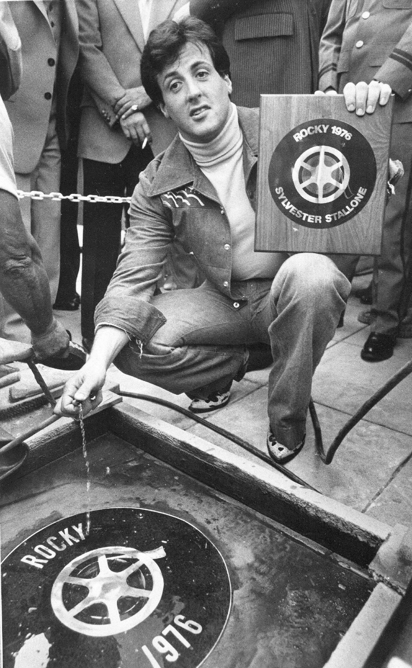 "HOLD FOR MONDAY, NOV. 21, STORY BY ERRIN HAINES WHACK – FILE – In this Sept. 22, 1977, file photo, actor and screenwriter Sylvester Stallone poses with a terrazzo inlay to be placed in the streets of the Westwood section of Los Angeles. Four decades after the Nov. 21, 1976, premiere of ""Rocky,"" the movie's reach is international, and the title character's underdog tale of determination, grit and sleepy-eyed charm still resonates with fans. (AP Photo, File)"