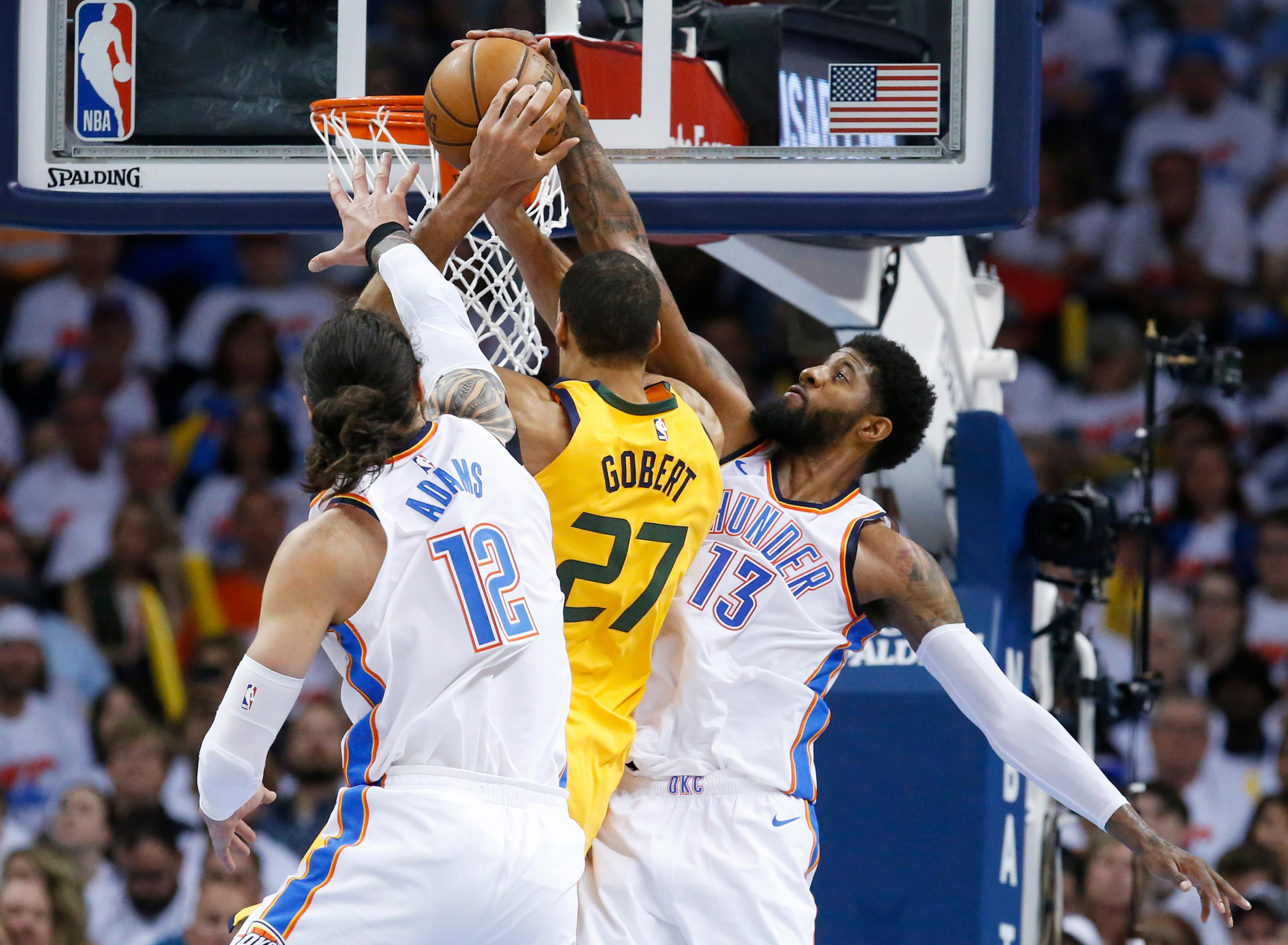 Oklahoma City Thunder forward Paul George (13) blocks a shot by Utah Jazz center Rudy Gobert (27) during the first half of Game 2 of an NBA basketball first-round playoff series in Oklahoma City, Wednesday, April 18, 2018. Thunder center Steven Adams (12) is at left. (AP Photo/Sue Ogrocki)
