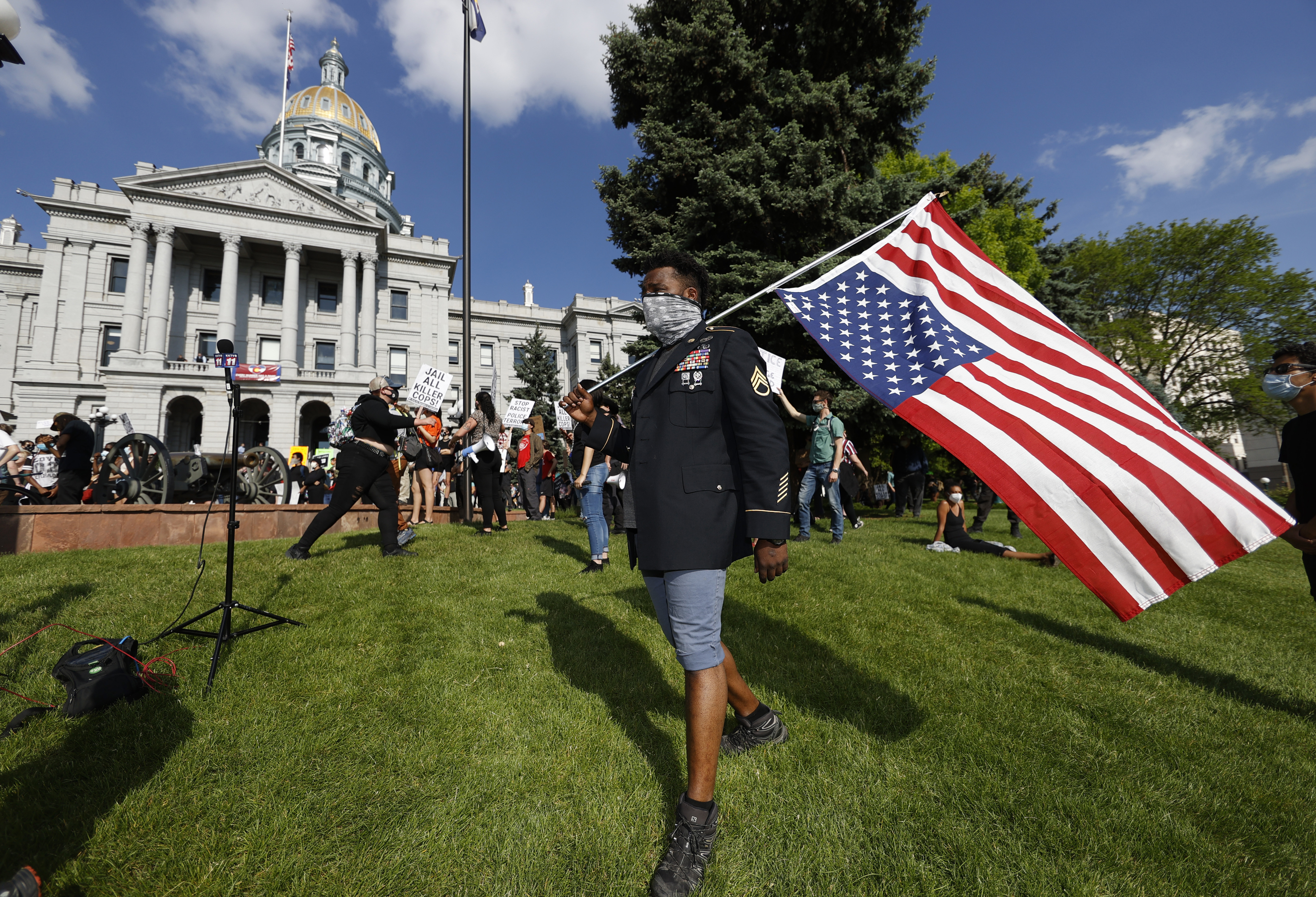 Aubrey Rose, who earned the rank of staff sergeant while serving four tours of duty in the U.S. Army, carries a flag during a protest outside the State Capitol over the death of George Floyd, a handcuffed black man in police custody in Minneapolis, Thursday, May 28, 2020, in Denver. Close to 1,000 protesters walked from the Capitol down the 16th Street pedestrian mall during the protest. (AP Photo/David Zalubowski)
