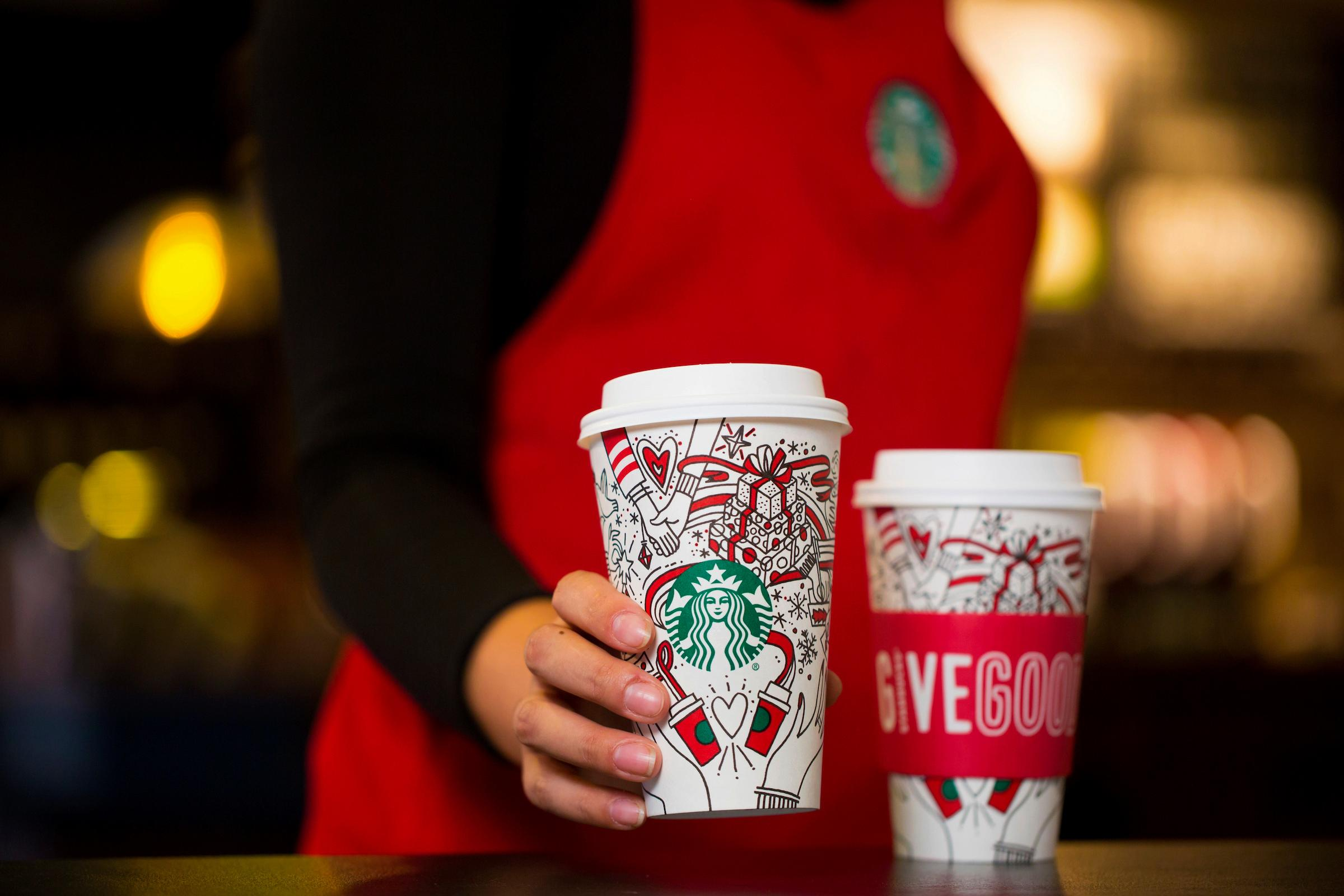 This Monday, Oct. 23, 2017, photo provided by Starbucks shows the company's 2017 holiday cup on display in Seattle. This latest holiday cup is mostly white, for customers to color in themselves. (Joshua Trujillo/Starbucks via AP)