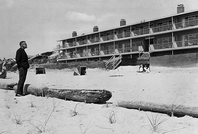 "Governor Tom McCall looks at Cannon Beach's Surfsand Motel in 1967. The owner, Bill Hay, wanted this beach area for the use of motel guests only. He set up a log perimeter and instructed his ""Cabana Boys"" and other employees to tell people who were not staying at the motel to leave the ""private beach."" The action exposed a loophole in existing state law and sparked a legislative conflict about public access to beaches. The Beach Bill was the product of the debate that pitted proponents of property rights against those favoring more public access protections. (Courtesy Oregon Historical Society)"
