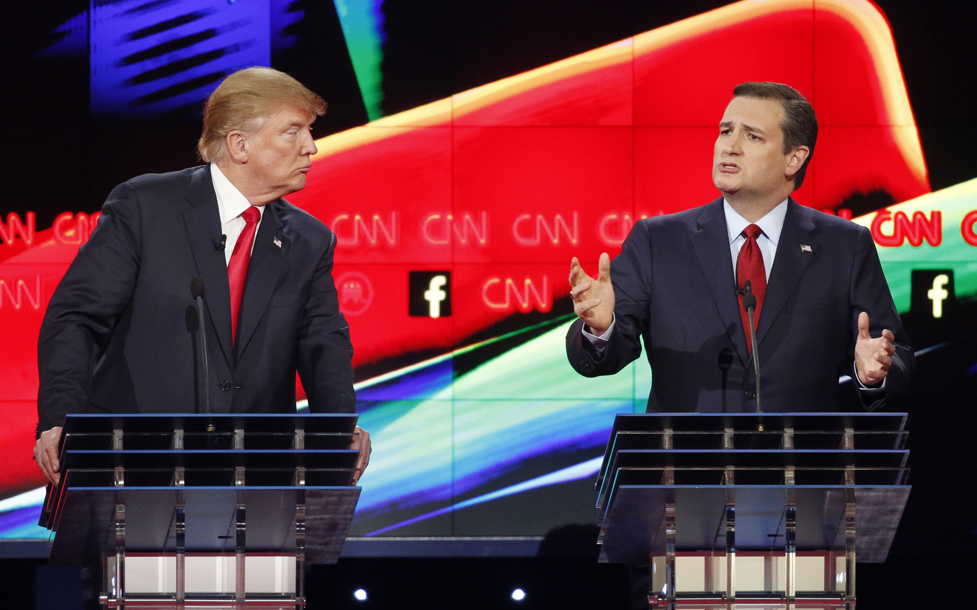 In this Dec. 15, 2015 photo, Donald Trump, left, watches as Ted Cruz speaks during the CNN Republican presidential debate at the Venetian Hotel & Casino in Las Vegas. A growing debate over AmericaÂ?s role in promoting regime change in the Middle East is creating unusual alliances among 2016 presidential candidates that cross party lines.  (AP Photo/John Locher)