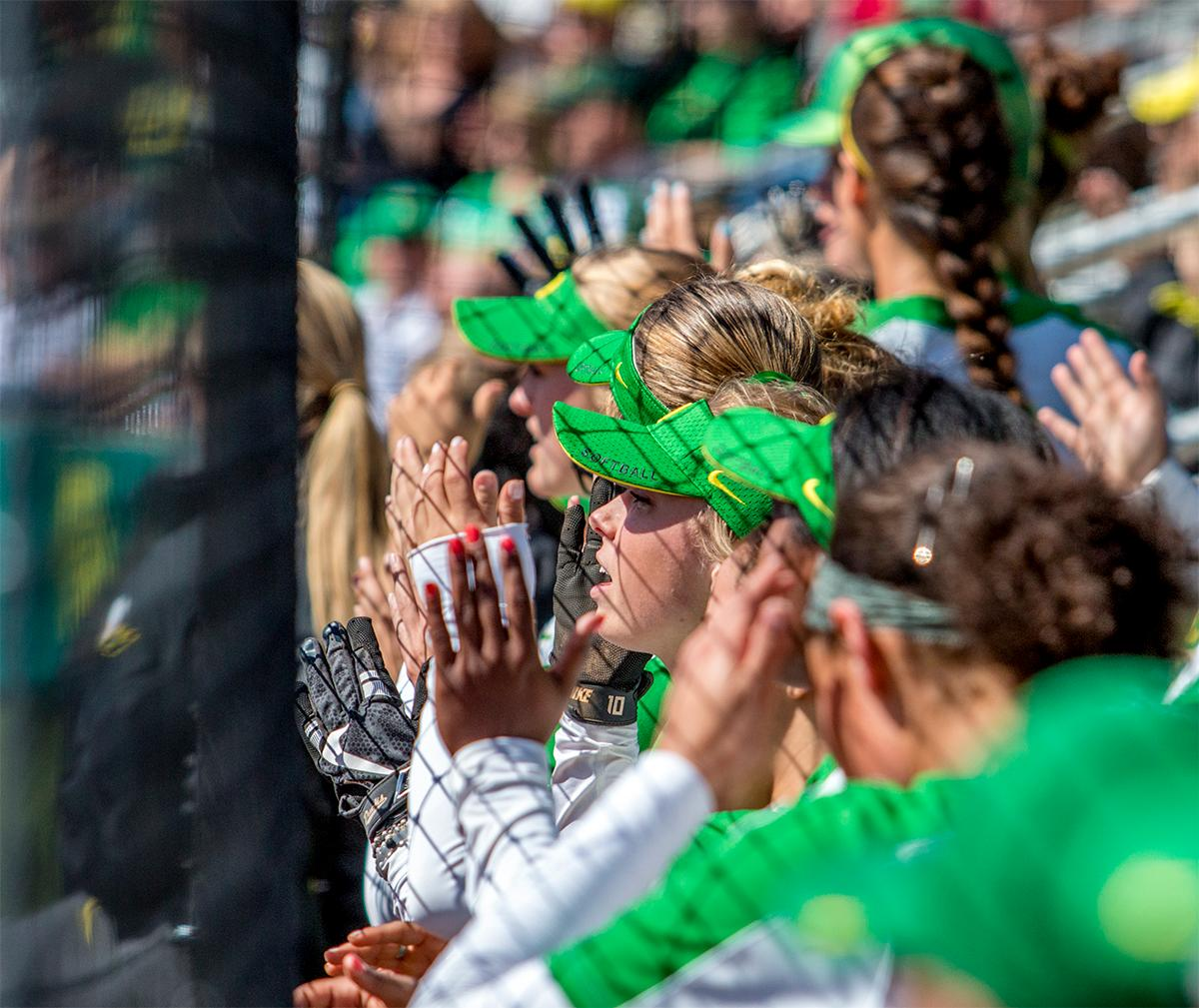 The Ducks team in the dugout cheer on their teammates on the field. The Oregon Ducks Softball team took their third win over the Arizona Sun Devils, 1-0, in the final game of the weekends series that saw the game go into an eighth inning before the Duck?s Mia Camuso (#7) scored a hit allowing teammate Haley Cruse (#26) to run into home plate for a point. The Ducks are now 33-0 this season and will next play a double header against Portland State on Tuesday, April 4 at Jane Sanders Stadium. Photo by August Frank, Oregon News Lab