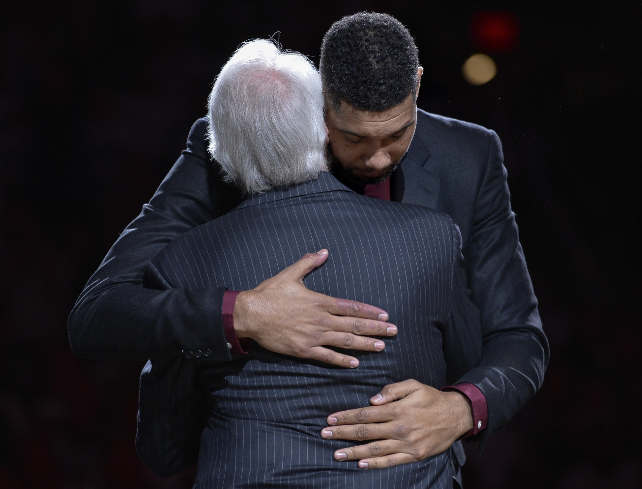 San Antonio Spurs legend Tim Duncan, right, hugs Spurs head coach Gregg Popovich during Duncan's jersey retirement ceremony, Sunday, Dec. 18, 2016, in San Antonio. (AP Photo/Darren Abate)