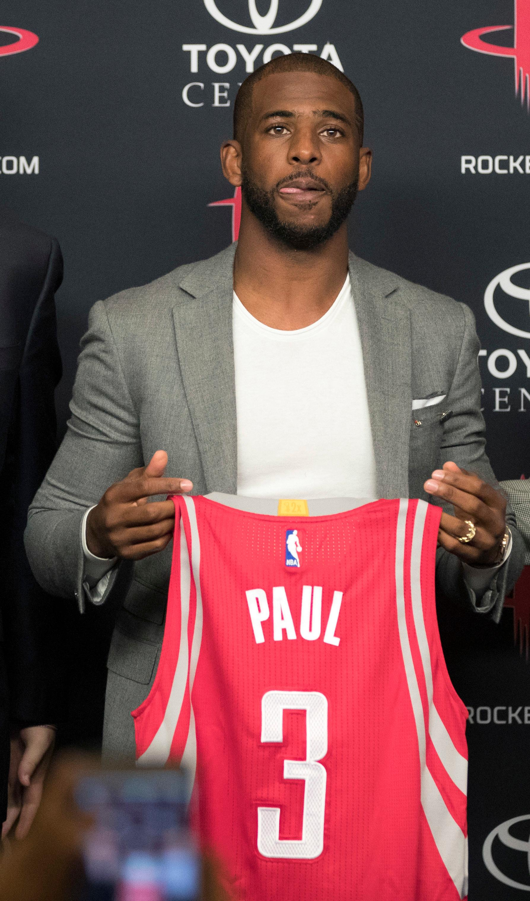 Chris Paul holds his new Houston Rockets jersey during a news conference Friday, July 14, 2017, in Houston. The nine-time All-Star was traded from the Los Angeles Clippers late last month. (AP Photo/David J. Phillip)