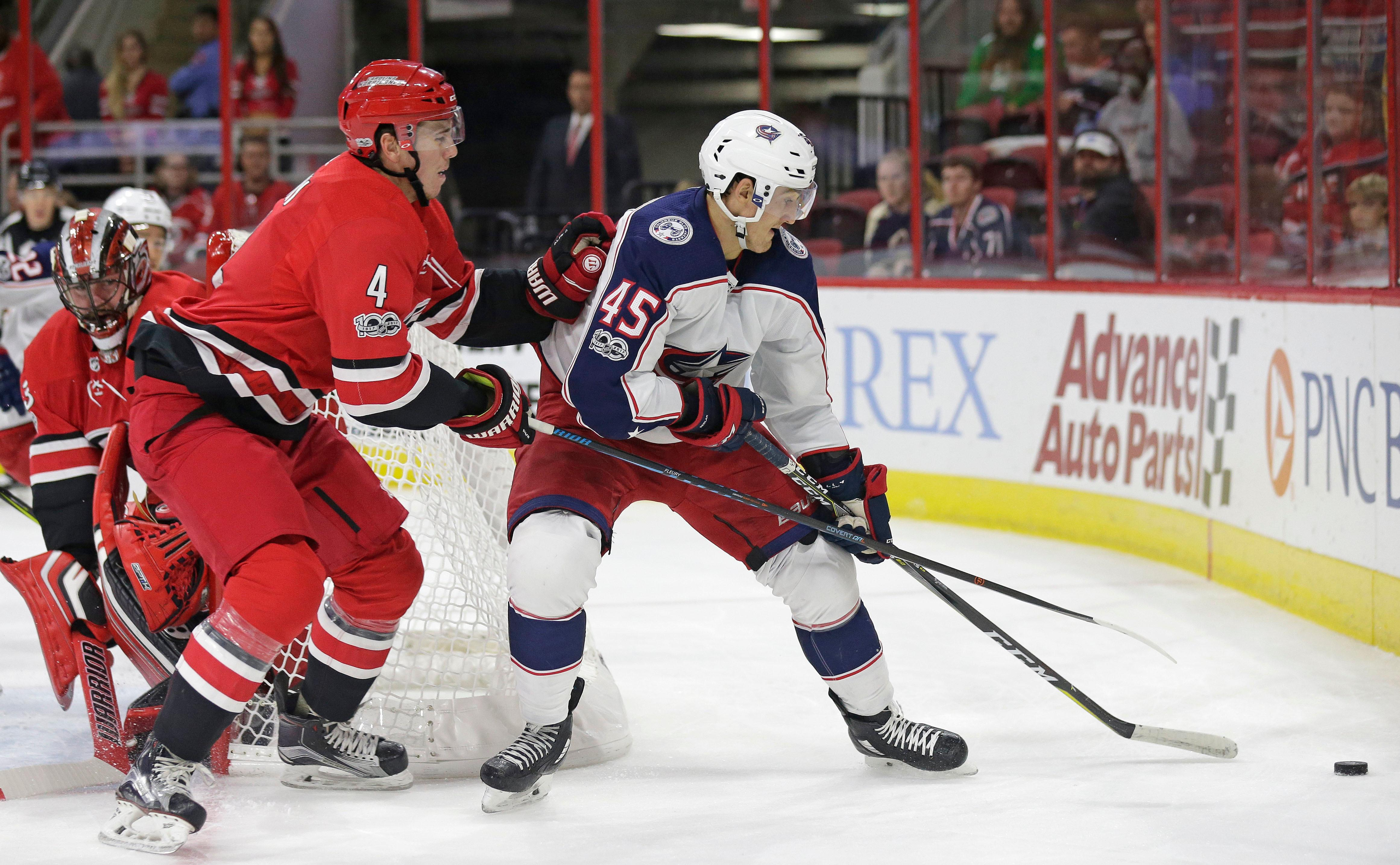 Carolina Hurricanes' Haydn Fleury (4) and Columbus Blue Jackets' Lukas Sedlak (45), of the Czech Republic, chase the puck during the first period of an NHL hockey game in Raleigh, N.C., Tuesday, Oct. 10, 2017. (AP Photo/Gerry Broome)