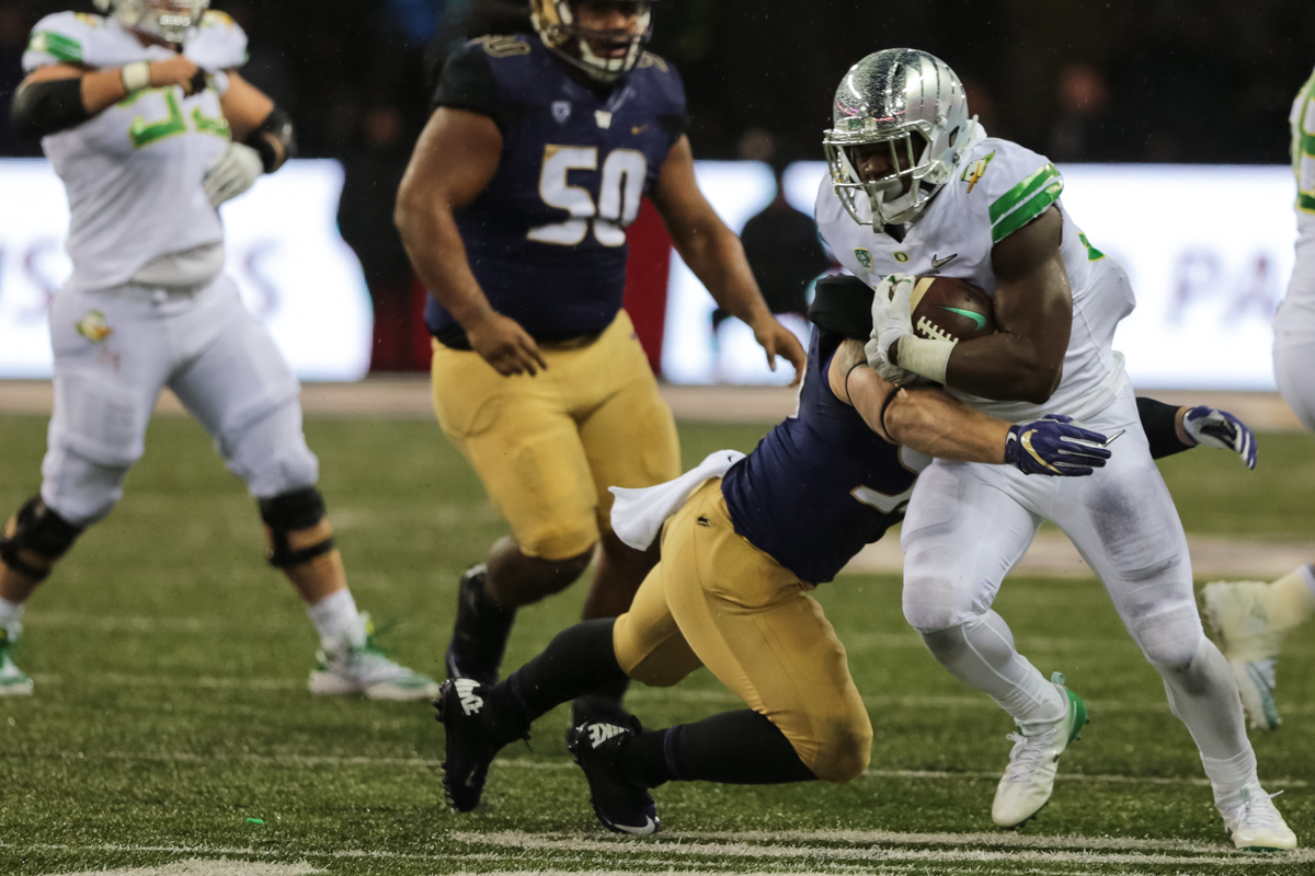 Oregon running back Royce Freeman (#21) is dragged down by a Washington defender. The Oregon Ducks are trailing the Washington Huskies 3 - 17 at halftime.  The Huskies rallied with a 17-point second quarter after a slow first quarter on a cold and rainy night in Seattle, Washington.  Photo by Austin Hicks, Oregon News Lab