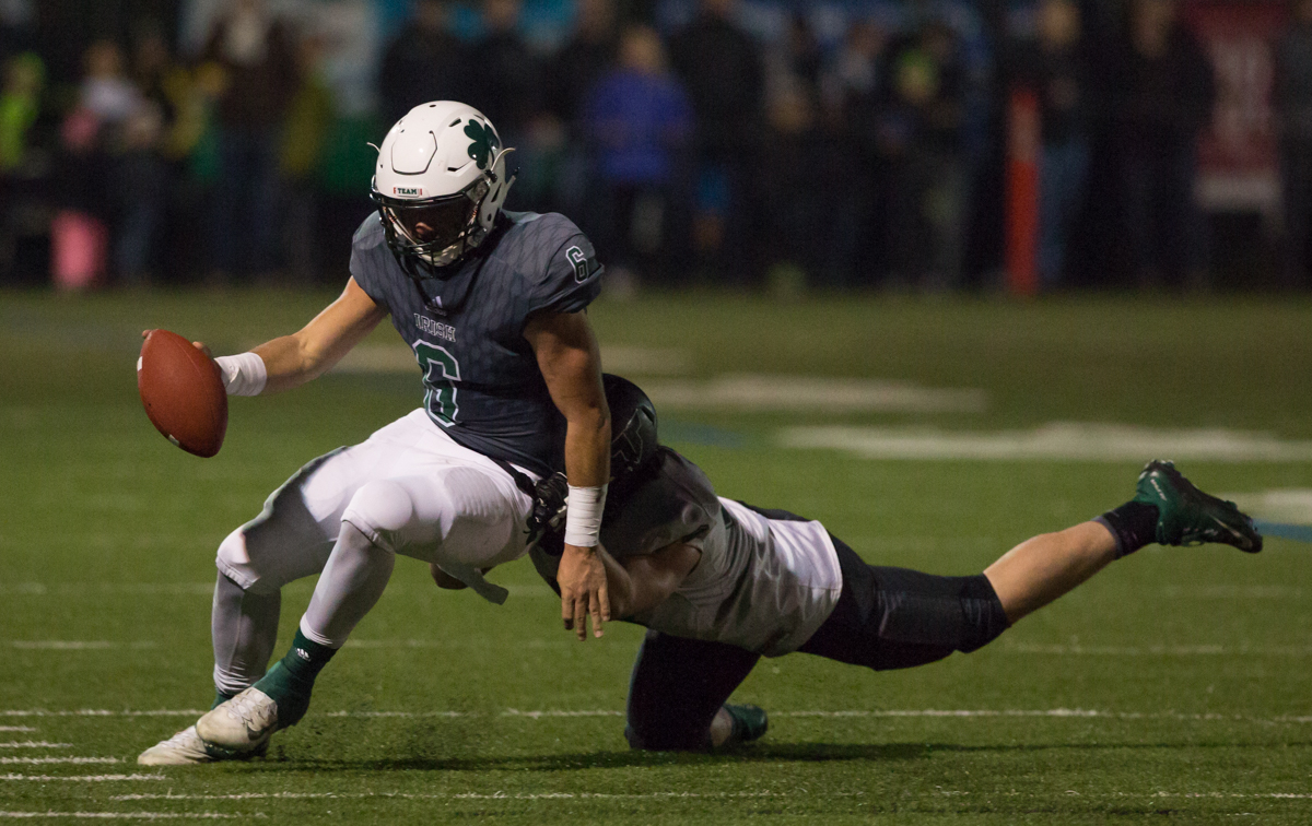Sheldon Irish quarterback Zach Diehl (#6) is dragged down by a Tigard defender.  The Tigard Tigers defeated Sheldon 27-0 to advance to the OSAA 6A semifinals.  Photo by Austin Hicks, Oregon News Lab