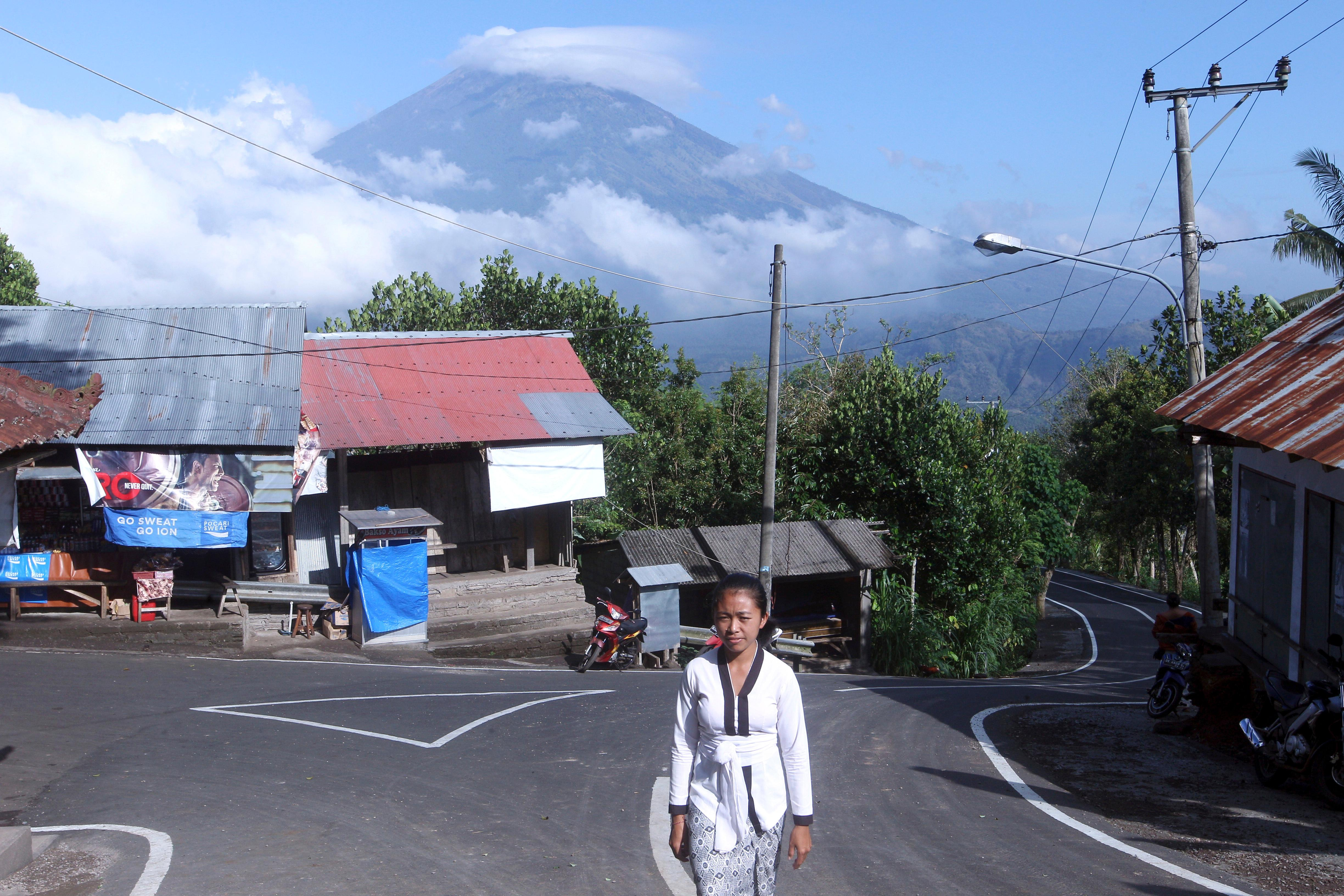 A Balinese woman walks toward a temple as Mount Agung volcano covered with clouds seen in the background at a village in Karangasem, Bali, Indonesia, Tuesday, Sept. 26, 2017. An increasing frequency of tremors from the volcano indicates magma is continuing to move toward the surface and an eruption is possible, a disaster agency official said Tuesday. Tourists are cutting short their stay to the island, where an eruption would force the airport to close and strand thousands. (AP Photo/Firdia Lisnawati)