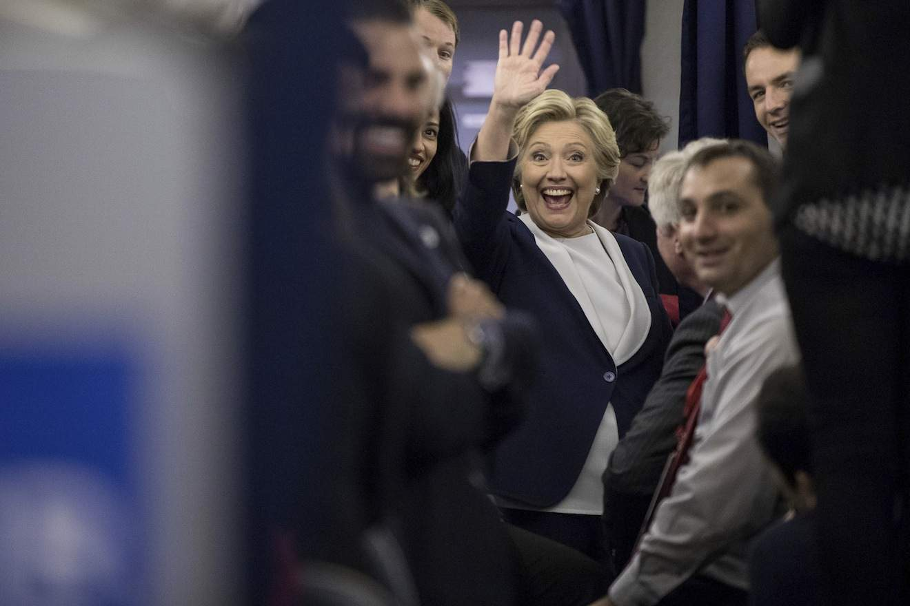Democratic presidential candidate Hillary Clinton waves to members of the media while aboard her campaign plane at LambertþÄìSt. Louis International Airport in St. Louis, N.Y., Sunday, Oct. 9, 2016, following the second presidential debate at Washington University. (AP Photo/Andrew Harnik)