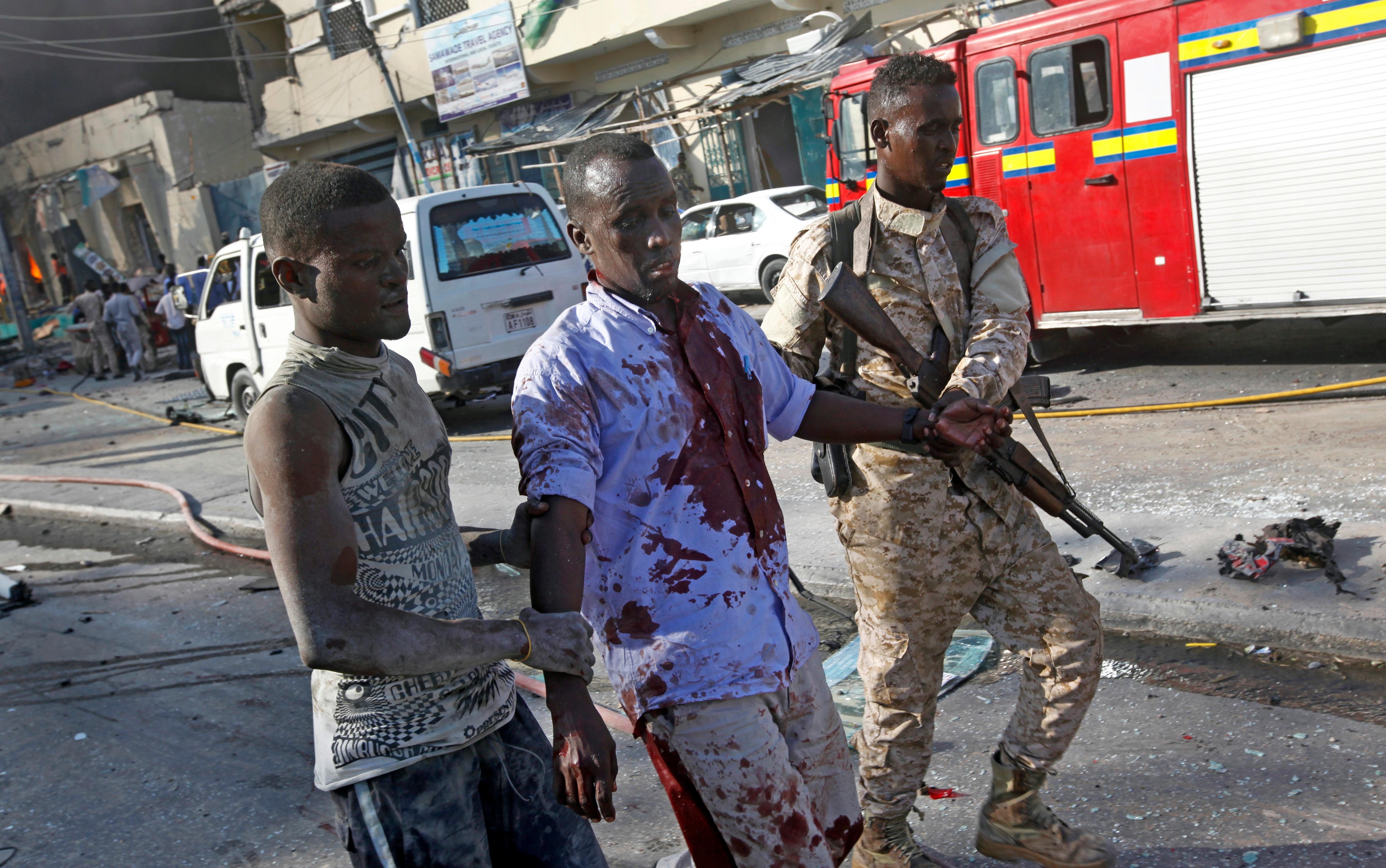 A Somali soldier helps a civilian wounded in a blast in the capital Mogadishu, Somalia Saturday, Oct. 14, 2017. A huge explosion from a truck bomb has killed at least 20 people in Somalia's capital, police said Saturday, as shaken residents called it the most powerful blast they'd heard in years. (AP Photo/Farah Abdi Warsameh)