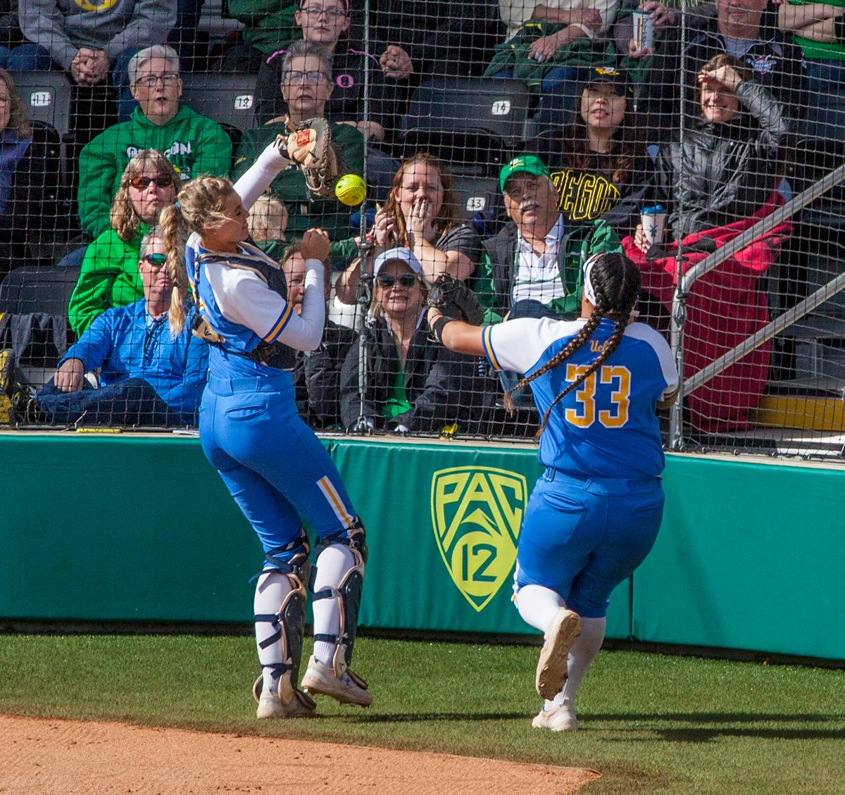The UCLA Bruins third baseman Brianna Tautalafua (#33) and catcher Paige Halstead (#25) attempt to catch a foul ball against the Ducks. The University of Oregon Ducks defeated the UCLA Bruins 3-0 in the final game of a three-game series Sunday afternoon at Jane Sanders Stadium. Shannon Rhodes hit a walk off three-run homer in the bottom of the 7th inning to win the game. The Ducks improved to 25-5 overall and 2-1 in Pac-12 play. Photo by William Tierney, Oregon News Lab