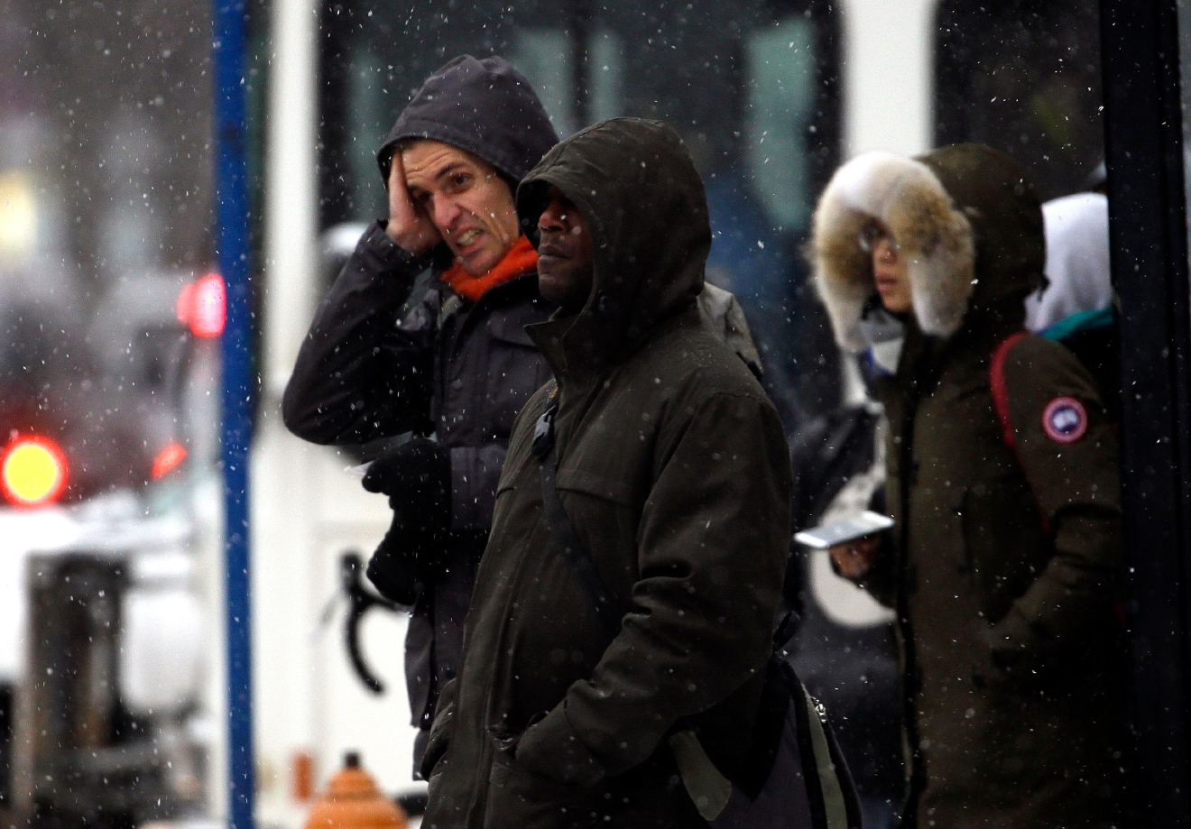 Bus riders, bundled against the cold, wait for the next ride as a snow storm moves in on the area in Portland, Ore., Wednesday, Dec. 14, 2016. A wintry afternoon and evening is forecast for much of Oregon, with some cities expected to get a foot of snow.(AP Photo/Don Ryan)
