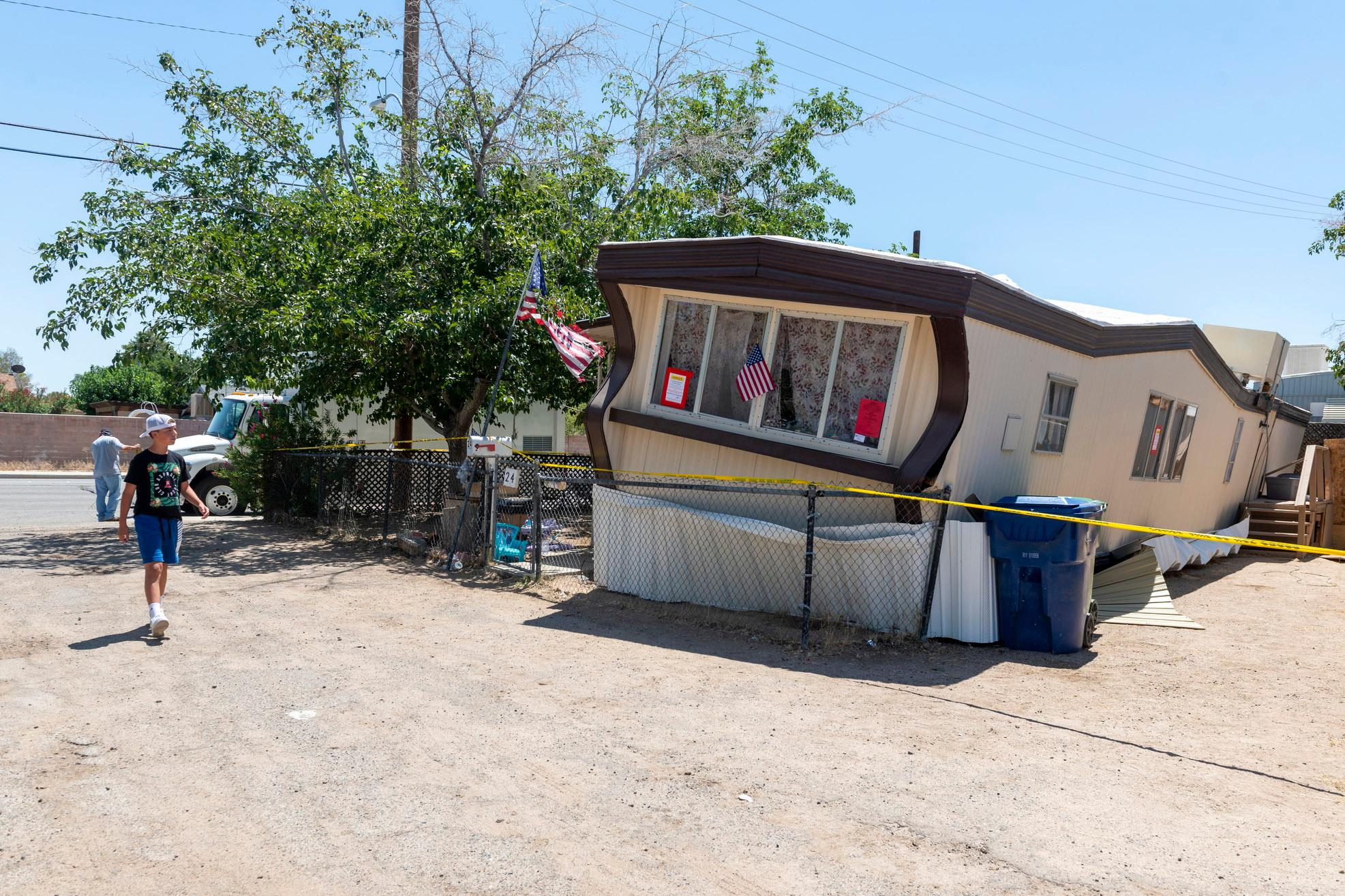 A child walks by one of the mobile homes knocked off its foundation by an earthquake in Ridgecrest, Calif., on Friday July 5, 2019. The strongest earthquake in 20 years shook a large swath of Southern California and parts of Nevada on the July 4th holiday, rattling nerves and causing injuries and damage in a town near the epicenter, followed by a swarm of ongoing aftershocks. The 6.4 magnitude quake struck Thursday morning in the Mojave Desert, about 150 miles northeast of Los Angeles, near the town of Ridgecrest. (James Quigg/The Daily Press via AP)