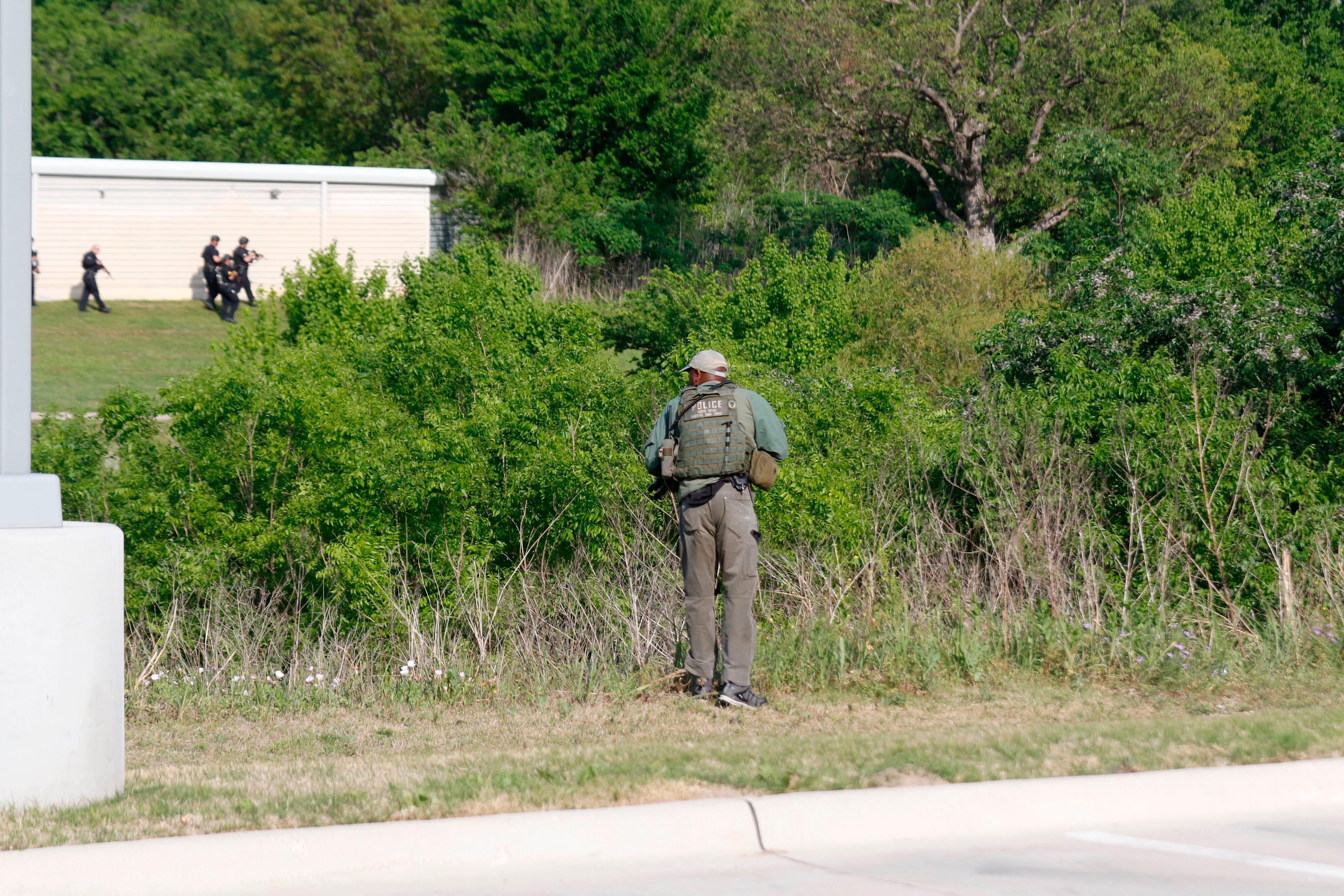 Dallas Police look for a suspect in the shooting of two police officers and a civilian Tuesday, April, 24,2018. Police are near ExtraSpace Storage, south of The Home Depot. Officer in the foreground is behind the Key-Whitman Eye Center on Central Expressway. (Ron Baselice/The Dallas Morning News via AP)
