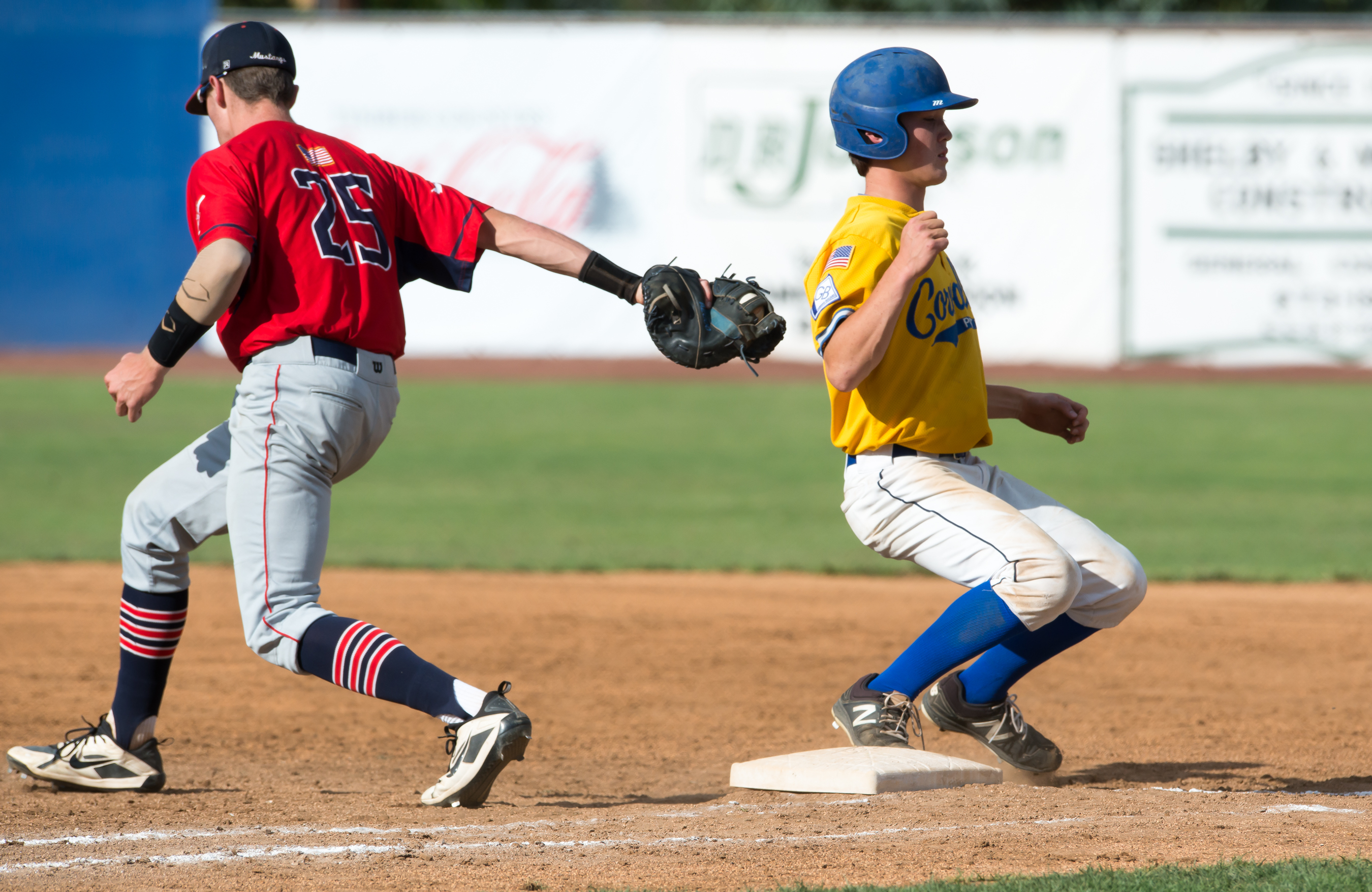 Medford first baseman Jacob Melton's swipe tag just misses Corvallis baserunner Franklin Leonard on a pickoff play in the eighth inning of Tuesday's game at Legion Field.