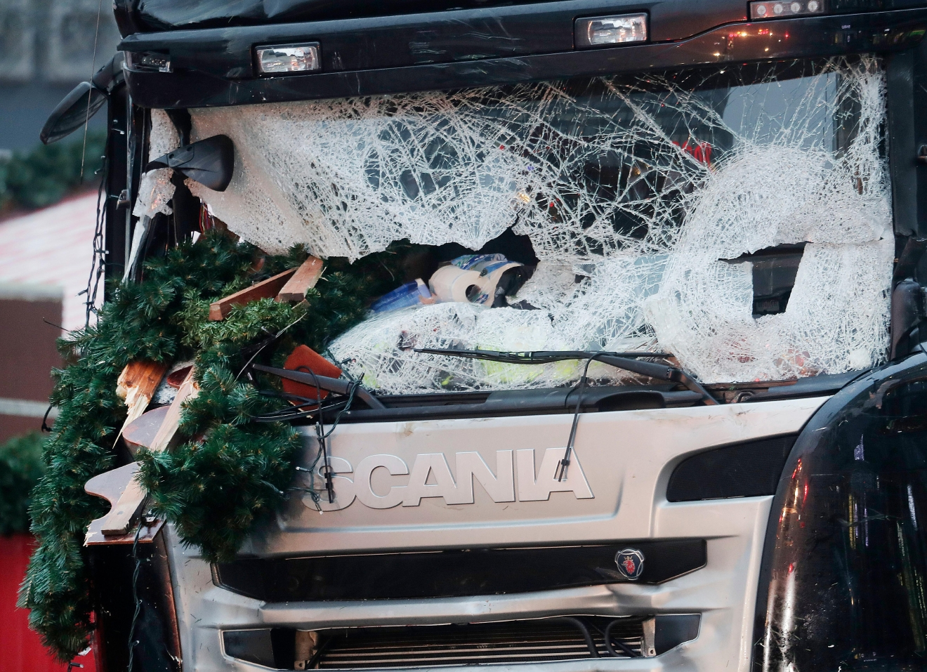 Christmas decoration sticks in the smashed window of the cabin of a truck which ran into a crowded Christmas market Monday evening killing several people in Berlin, Germany, Tuesday, Dec. 20, 2016. (AP Photo/Markus Schreiber)