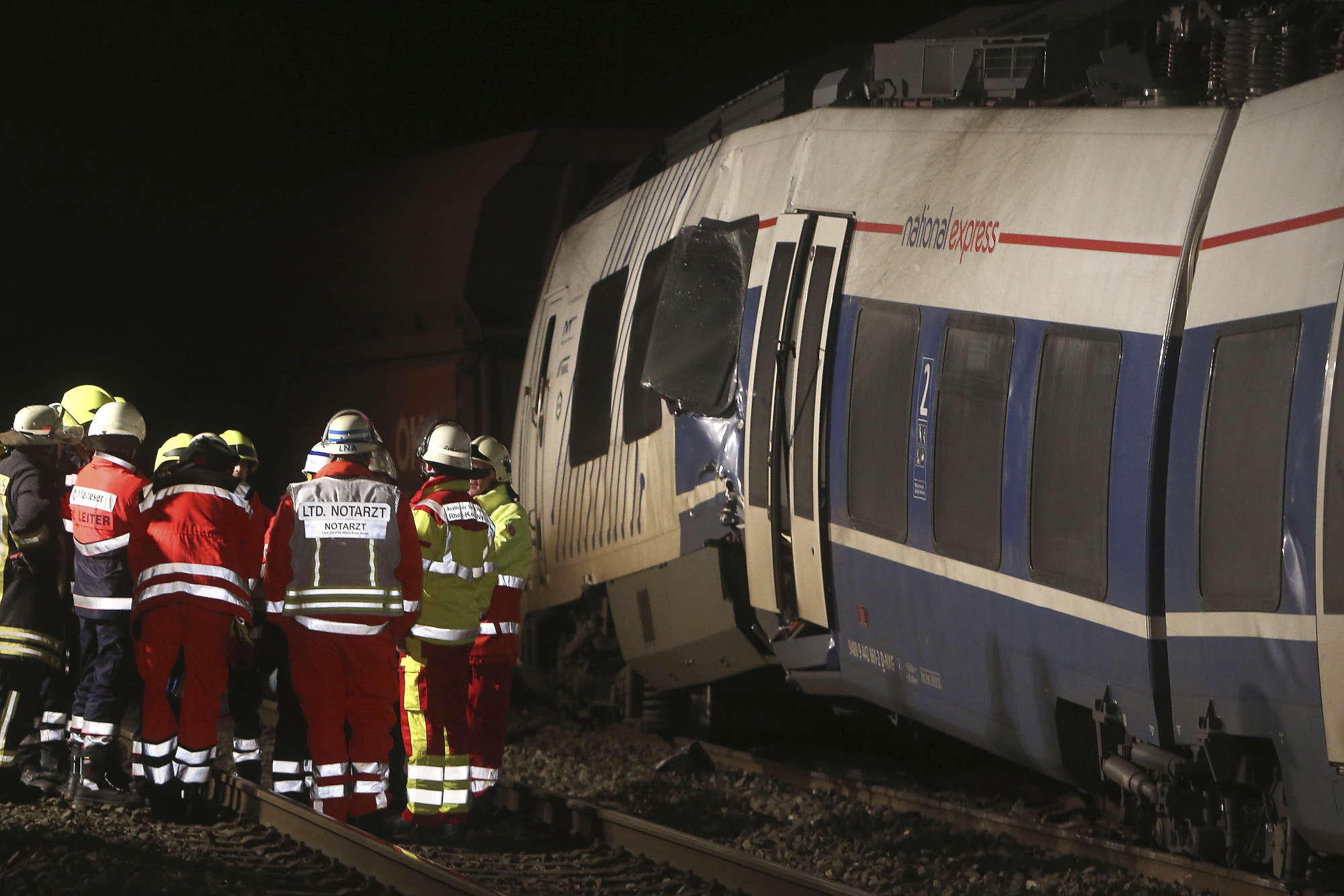 Firefighters stand beside a crashed train near Meerbusch, western Germany, Tuesday, Dec. 5, 2017. Several people have been injured when the passenger train collided with a cargo train. (David Young/dpa via AP)