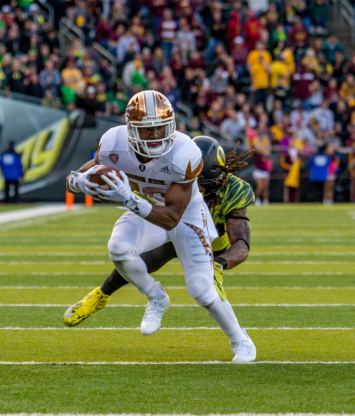 The Sun Devils' Kyle Williams (#10) runs the ball down the field as the Ducks tackle him. The Oregon Ducks broke their losing streak by defeating the ASU Sun Devils on Saturday 54-35. Photo by August Frank, Oregon News Lab