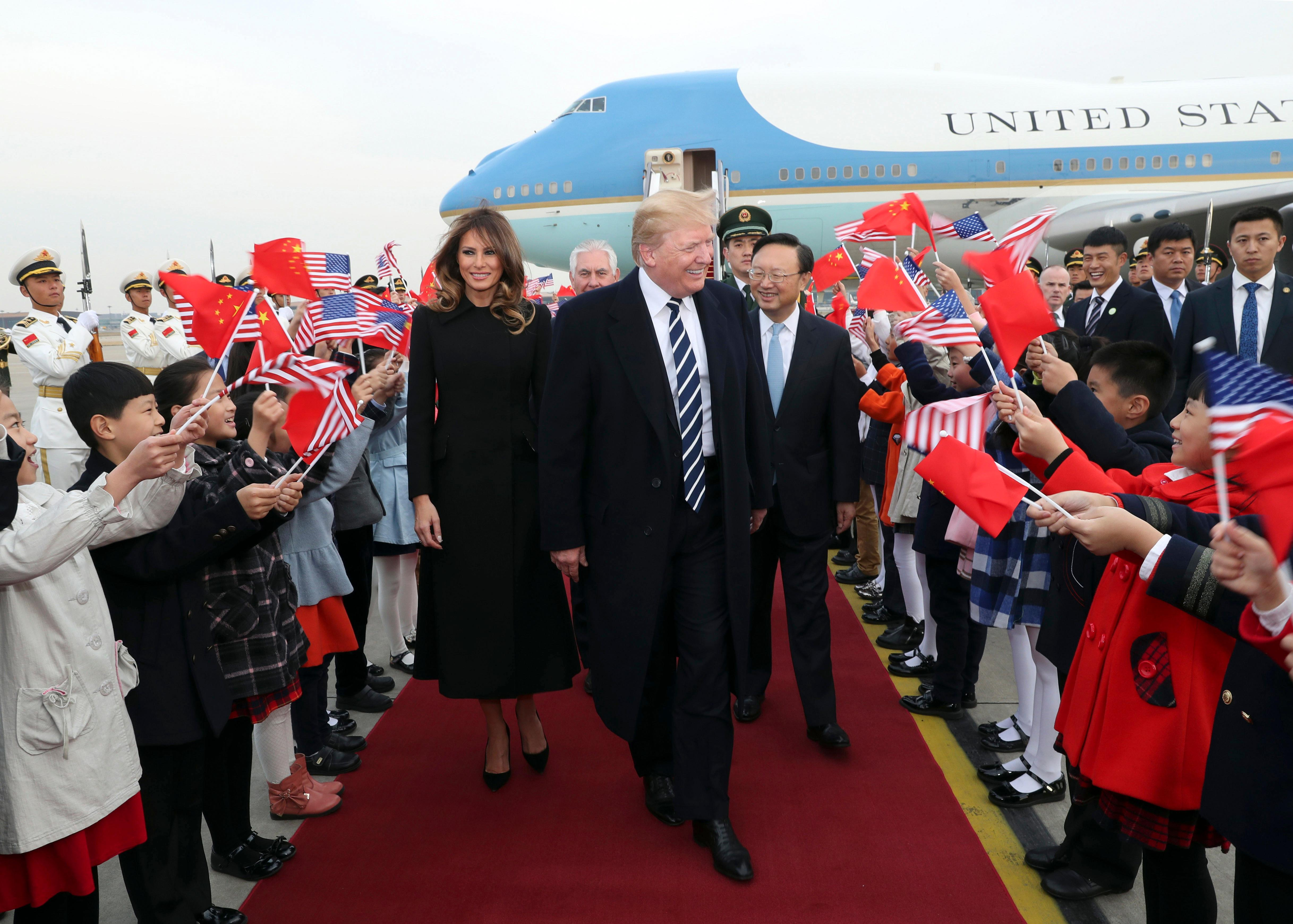 In this photo released by Xinhua News Agency, children wave U.S. and Chinese flags as U.S. President Donald Trump and first lady Melania Trump arrive at Beijing Airport, Wednesday, Nov. 8, 2017, in Beijing. Trump is on a five-country trip through Asia traveling to Japan, South Korea, China, Vietnam and the Philippines. (Pang Xinglei/Xinhua via AP)