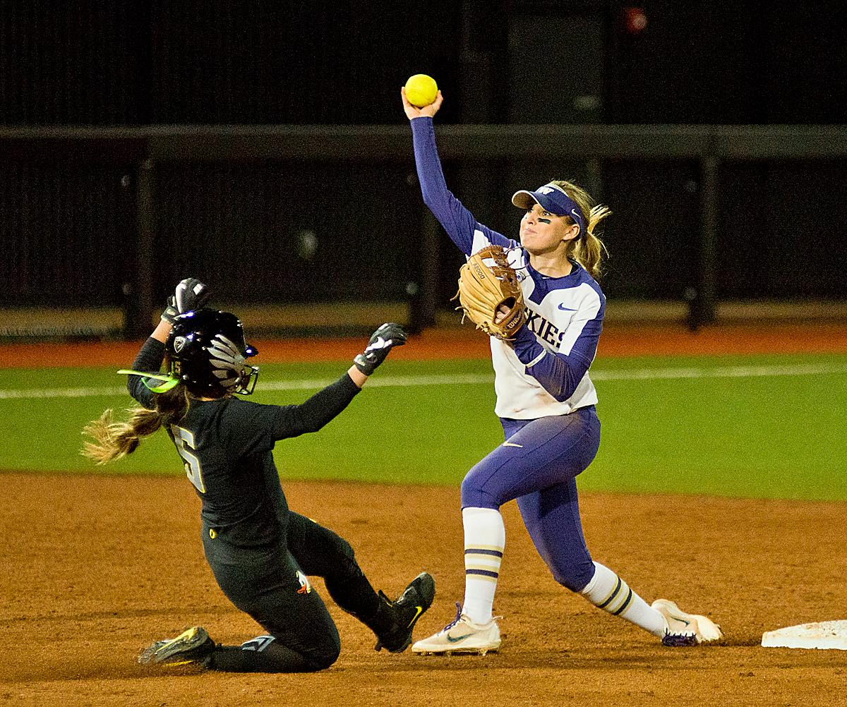 Ducks Sammie Puentes (#5) is out at second as Huskies Ali Aguilar attempts a double play. In Game Two of a three-game series, the University of Oregon Ducks softball team defeated the University of Washington Huskies 4-1 Friday night in Jane Sanders Stadium. Danica Mercado (#2), Alexis Mack (#10) and Mia Camuso (#7) all scored in the win, Mack twice. The Ducks play the Huskies for the tie breaker on Saturday with the first pitch at noon. Photo by Dan Morrison, Oregon News Lab