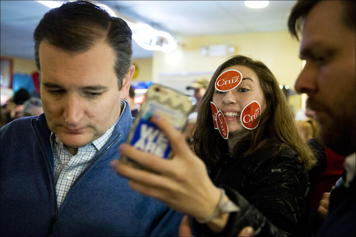 Delaney Anne tries to make a selfie with Republican presidential candidate, Sen. Ted Cruz, R-Texas, during a campaign stop, Monday, Jan. 18, 2016, in Tilton, N.H. (AP Photo/Matt Rourke)