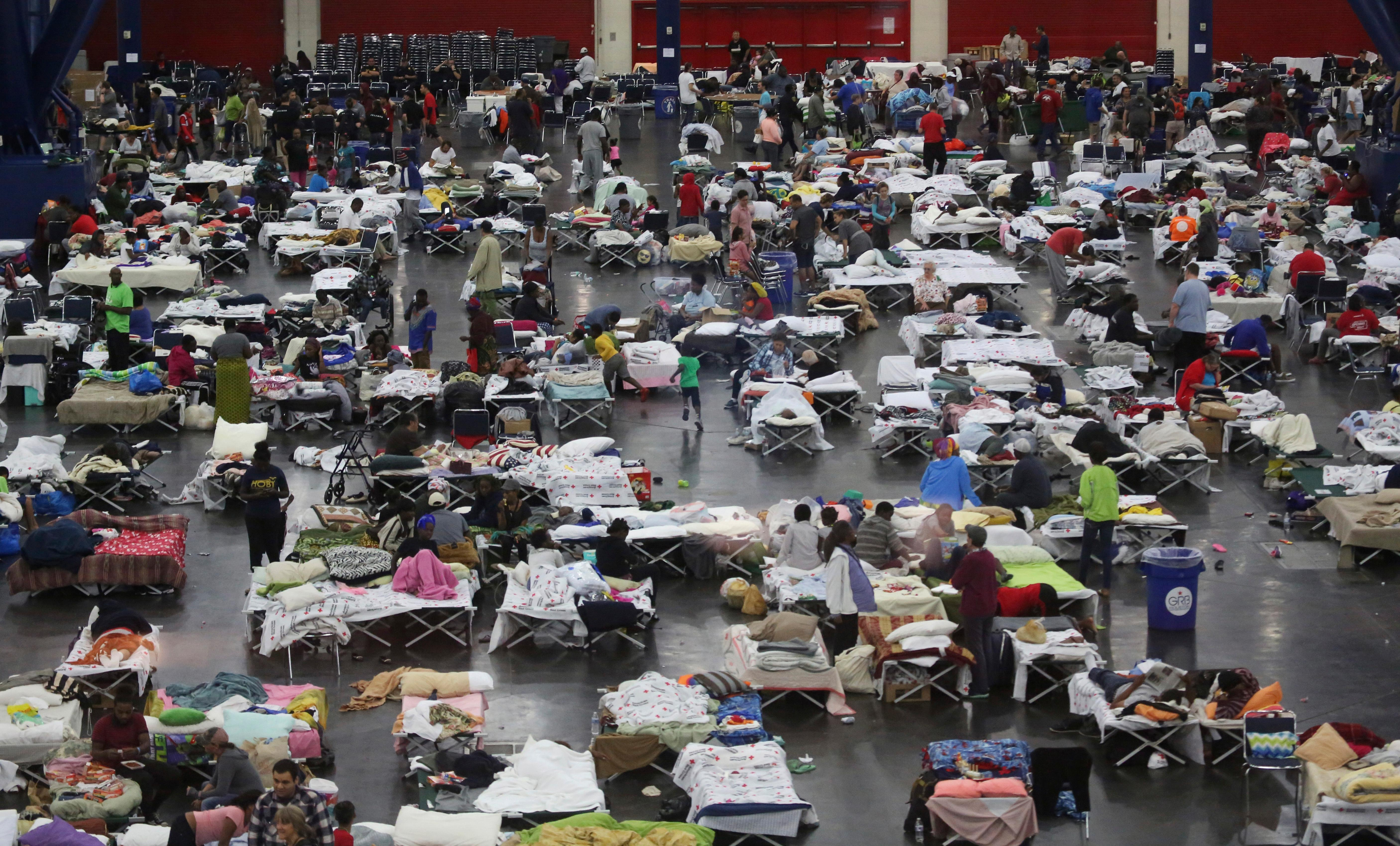FILE - In this Tuesday, Aug. 29, 2017, file photo, evacuees escaping the floodwaters from Tropical Storm Harvey rest at the George R. Brown Convention Center in Houston, Texas. Officials say the last 900 Hurricane Harvey evacuees at the George R. Brown Convention Center have been relocated as the site returns to regular business. (AP Photo/LM Otero, File)