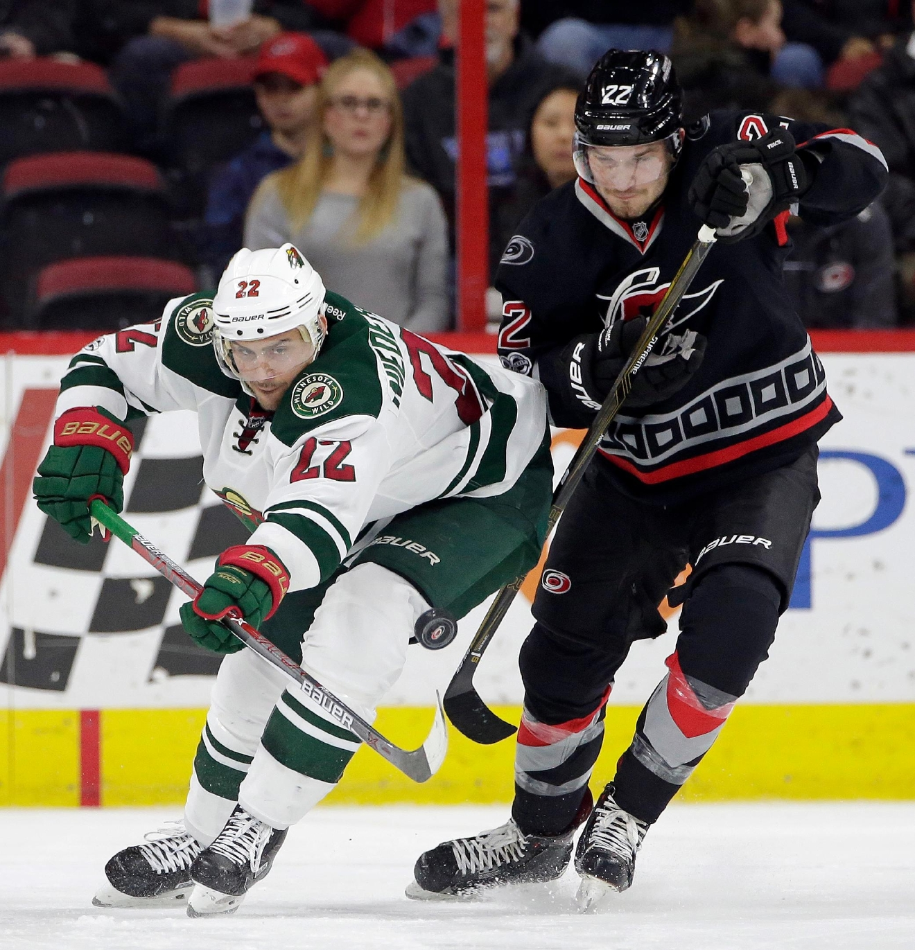 Carolina Hurricanes' Brett Pesce (22), right, and Minnesota Wild's Nino Niederreiter (22), of Switzerland, chase the puck during the second period of an NHL hockey game in Raleigh, N.C., Thursday, March 16, 2017. (AP Photo/Gerry Broome)
